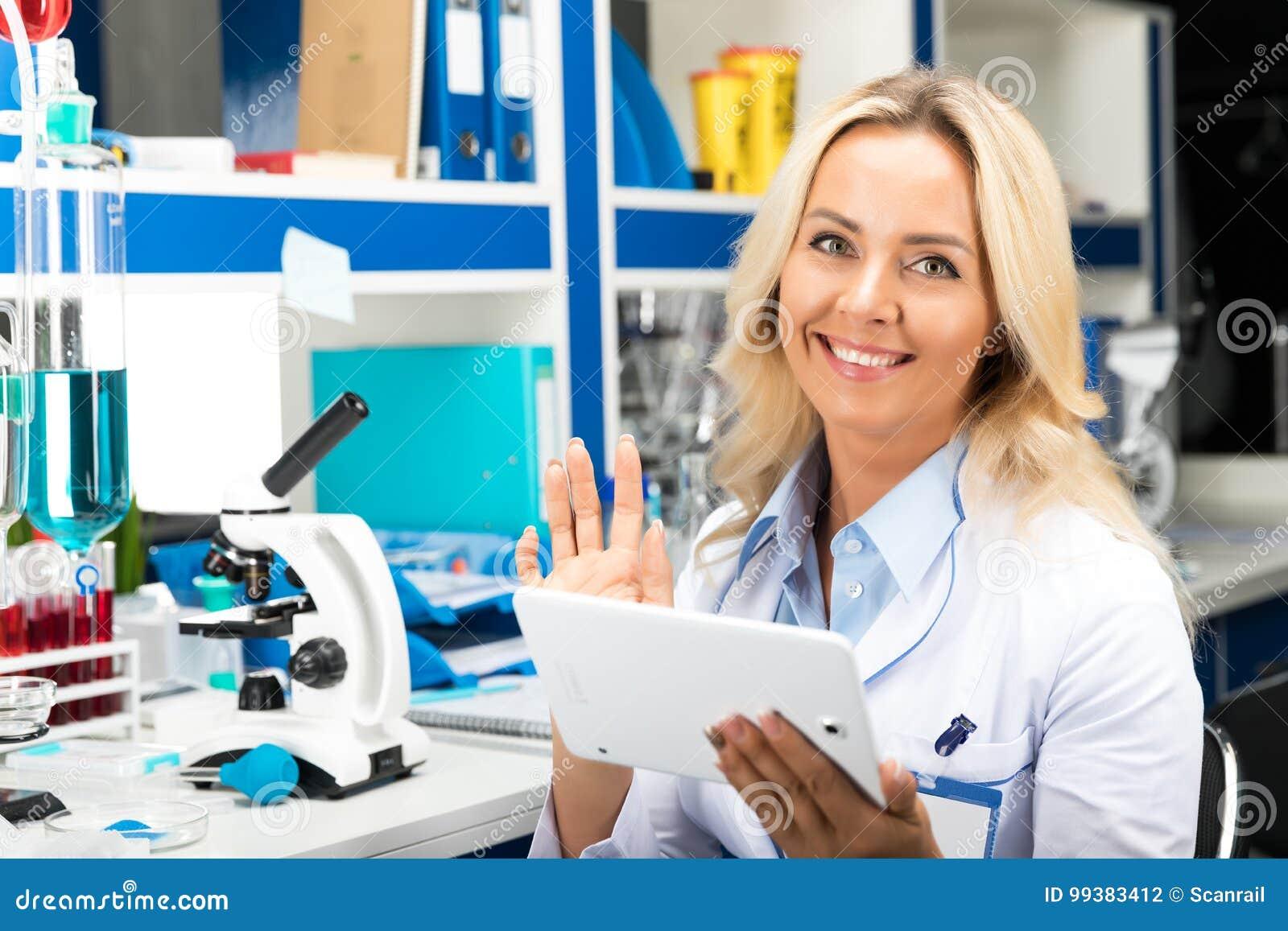Молодой привлекательный ученый женщины используя планшет в Ла