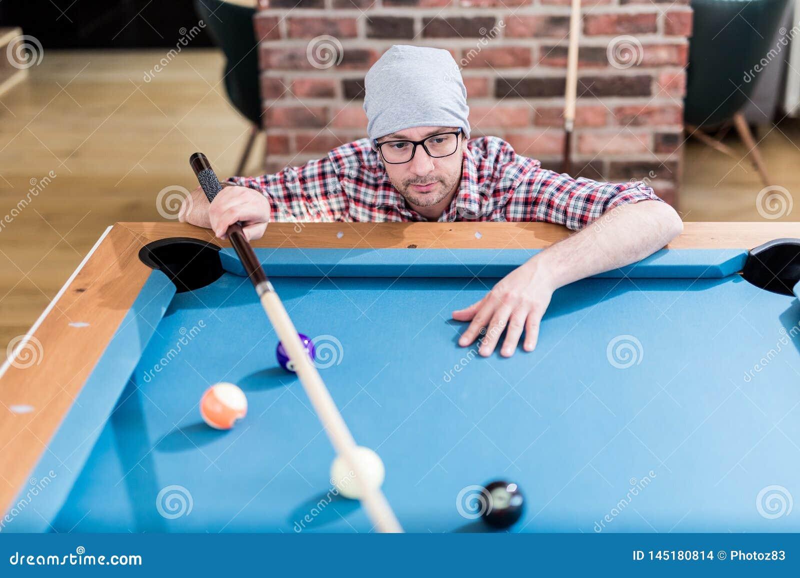 Молодой современный модный человек смотря шарики билльярдов бассейна