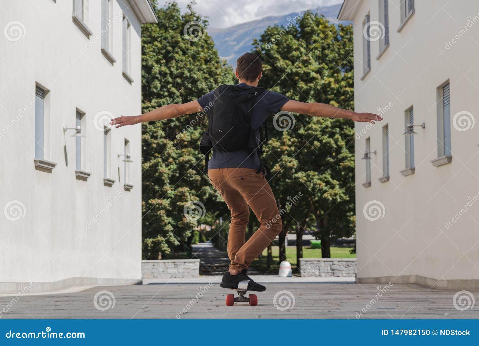 Молодой счастливый человек с рюкзаком используя longboard для идти обучить после летних отпусков