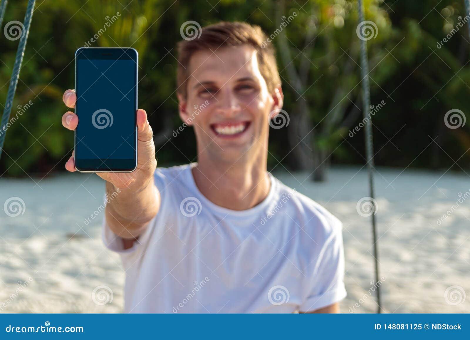 Молодой счастливый человек усаженный на качание показывая вертикальный экран телефона Белые песок и джунгли как предпосылка