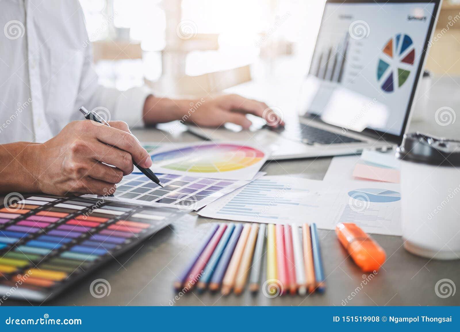 Молодой творческий график-дизайнер работая на образцах чертежа и цвета проекта архитектурноакустических, расцветке выбора на граф
