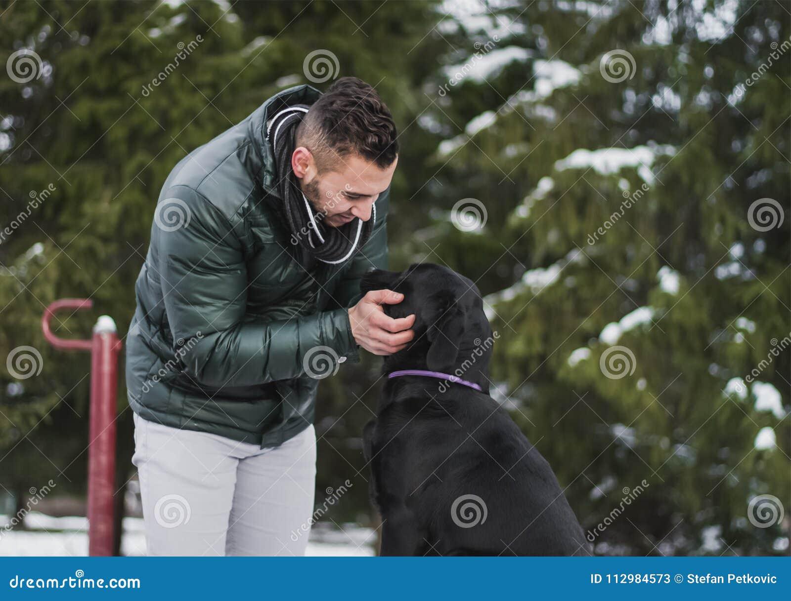 Молодой тренер собаки с черным labrador в парке