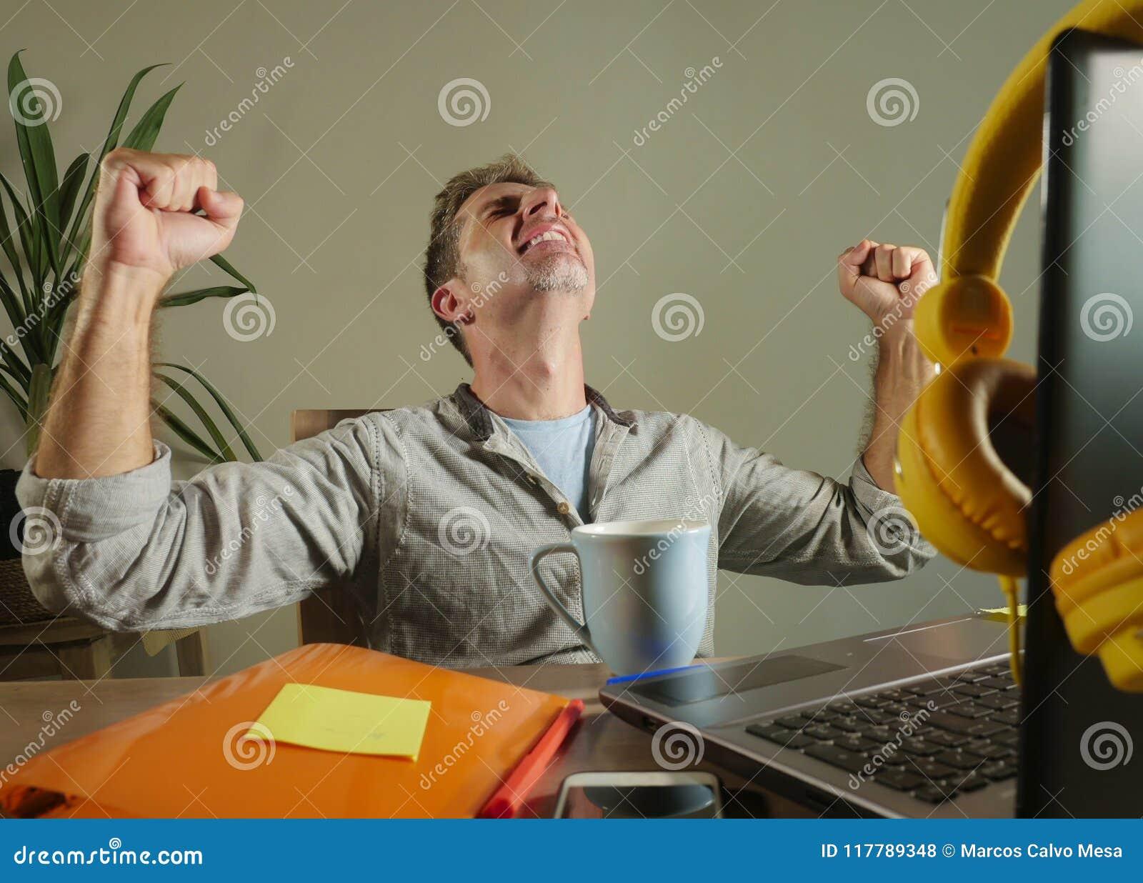 Молодой удовлетворенный и уверенно бизнесмен возбудил показывать на победе как победитель работая дома офис с портативным компьют