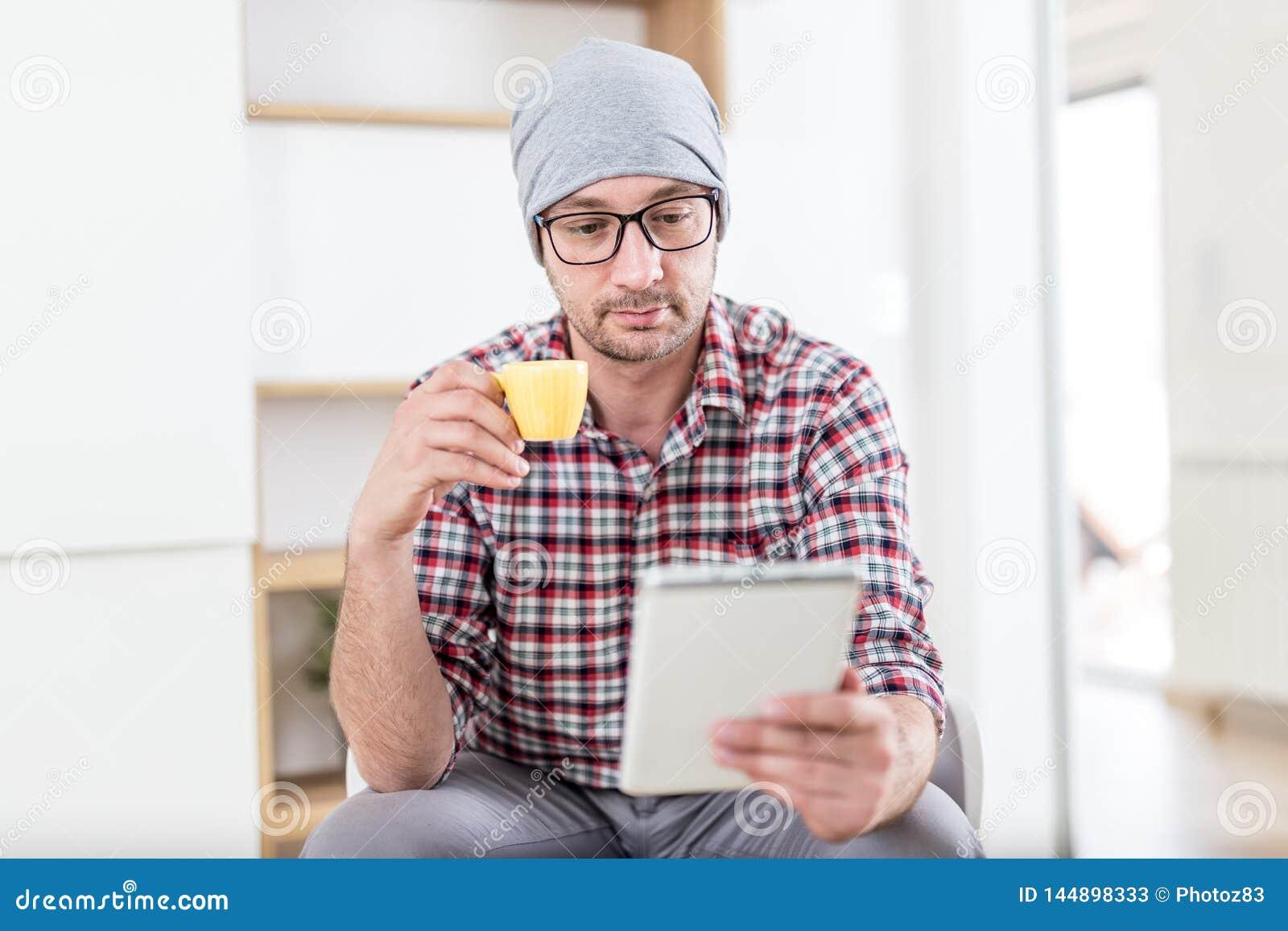 Молодой ультрамодный человек сидя на офисе и наслаждаясь его кофе утр