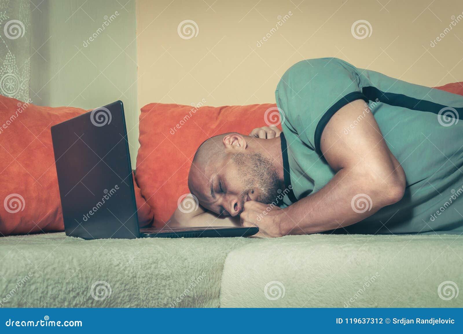 Молодой утомленный человек принимая пролом и упал уснувший на кровати с его компьютером верхней части подола после того как трудн