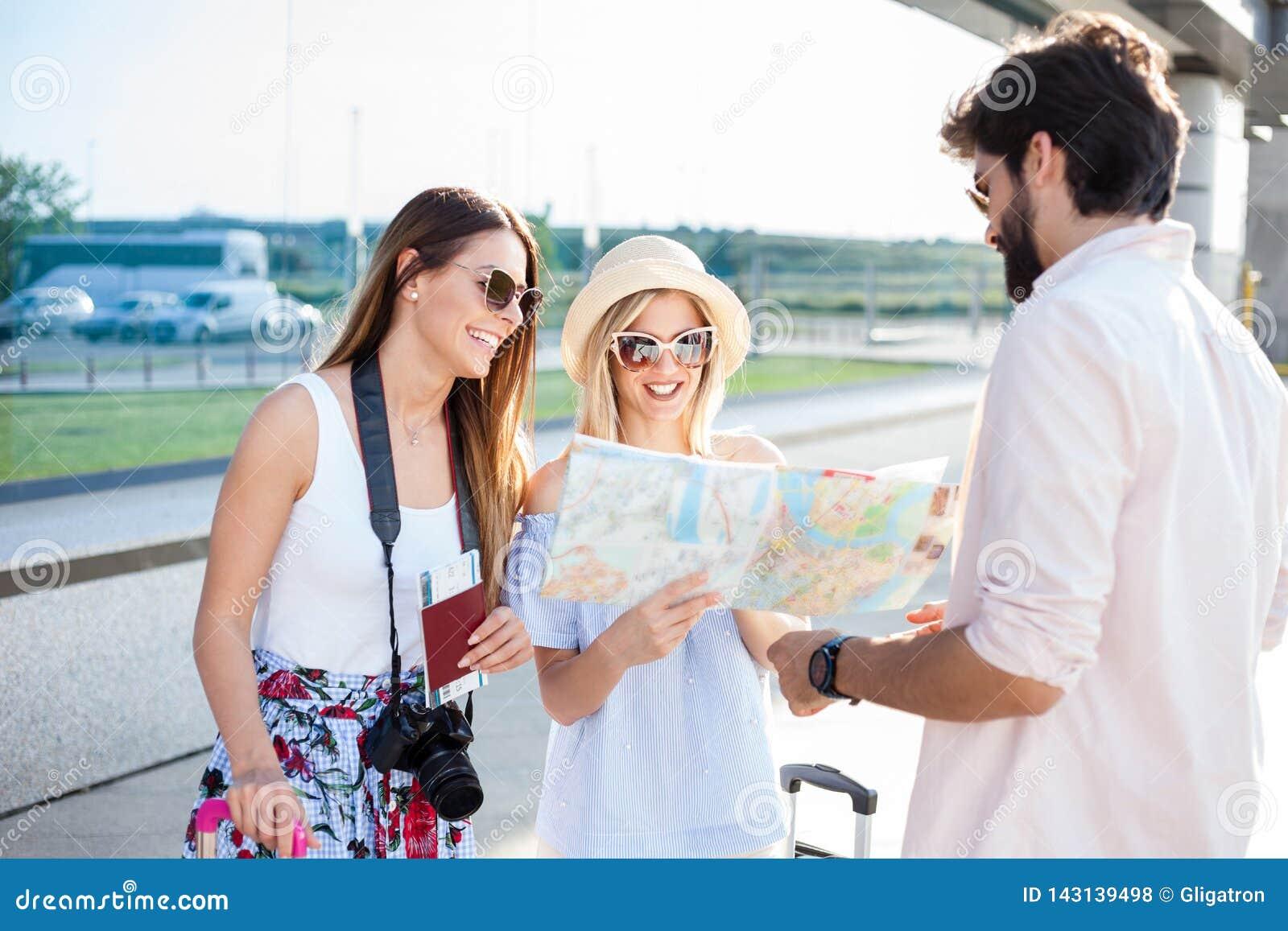 Молодой человек давая направления до 2 красивых молодых женских туриста