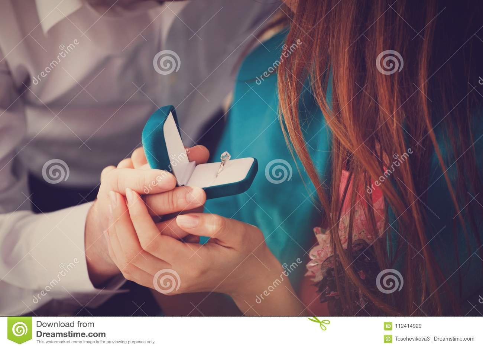 Молодой человек делает предложение руки и сердца к его подруге и удивляет ее с красивым обручальным кольцом