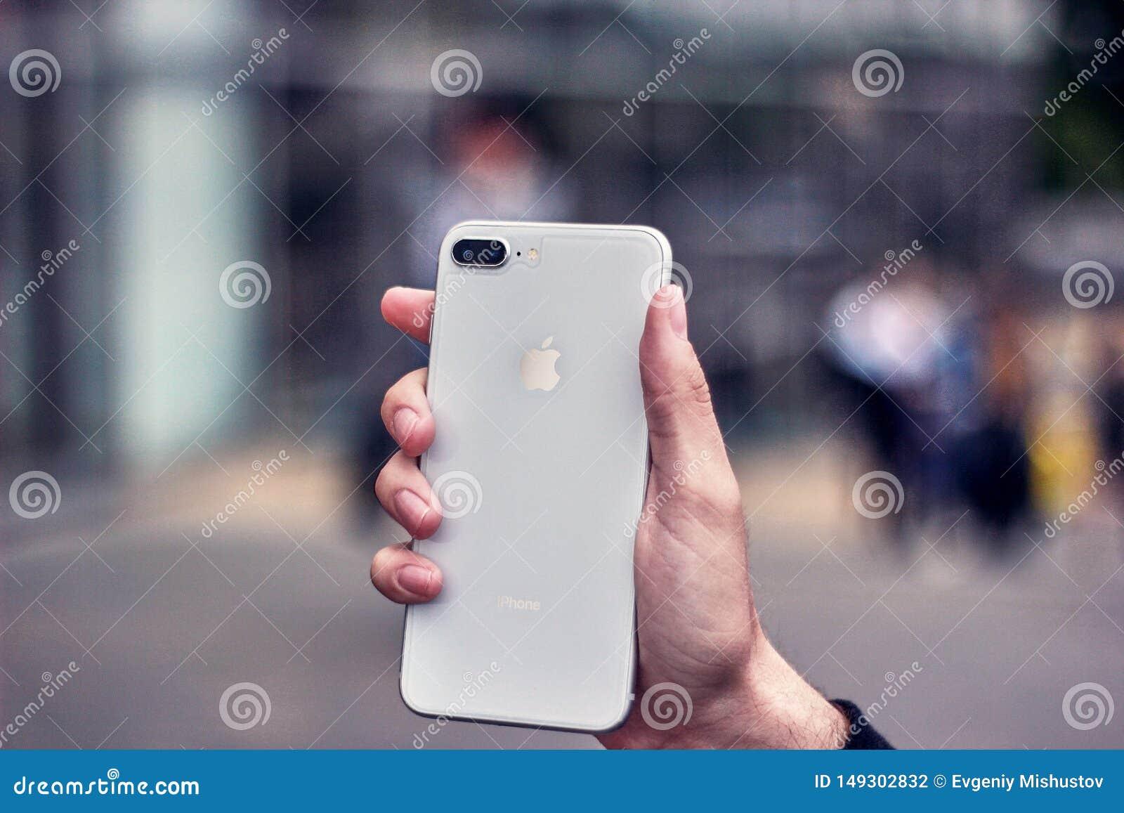 Молодой человек держа белое iphone на предпосылке запачканного города