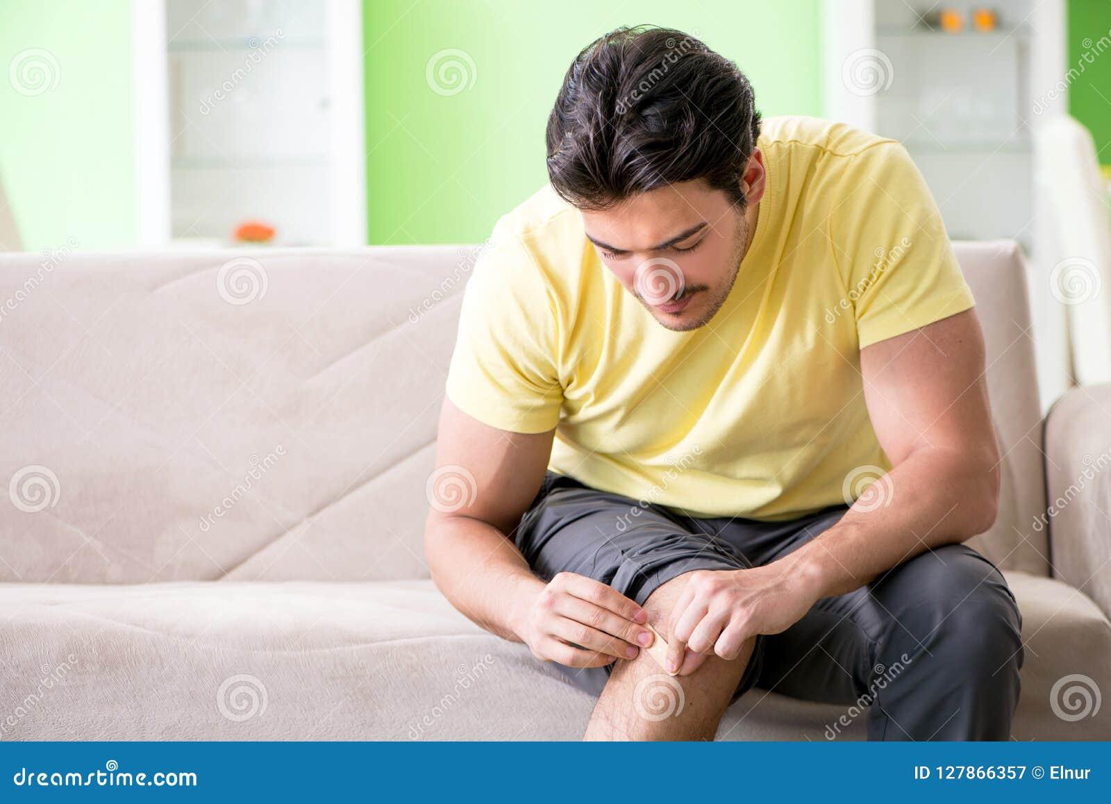 Молодой человек дома после ушиба