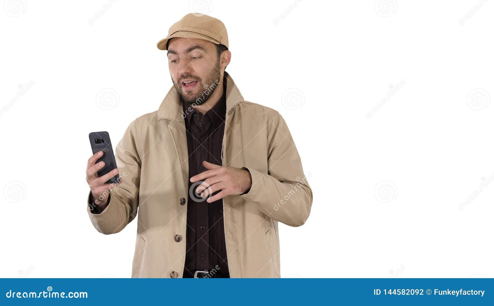 Молодой человек звоня видео- из его мобильного телефона пока идущ на белой предпосылке