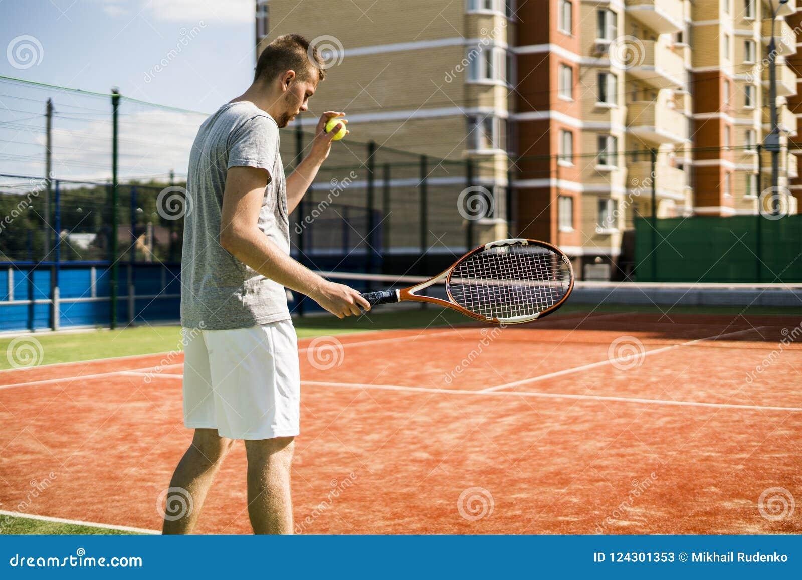 Молодой человек играя теннис на суде в дворе здания апартаментов внешнем