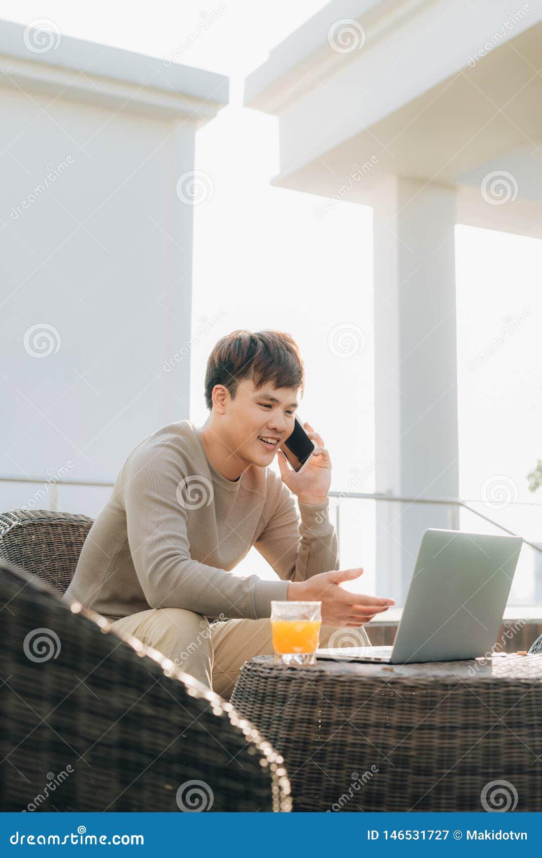 Молодой человек используя ноутбук пока сидящ на софе снаружи