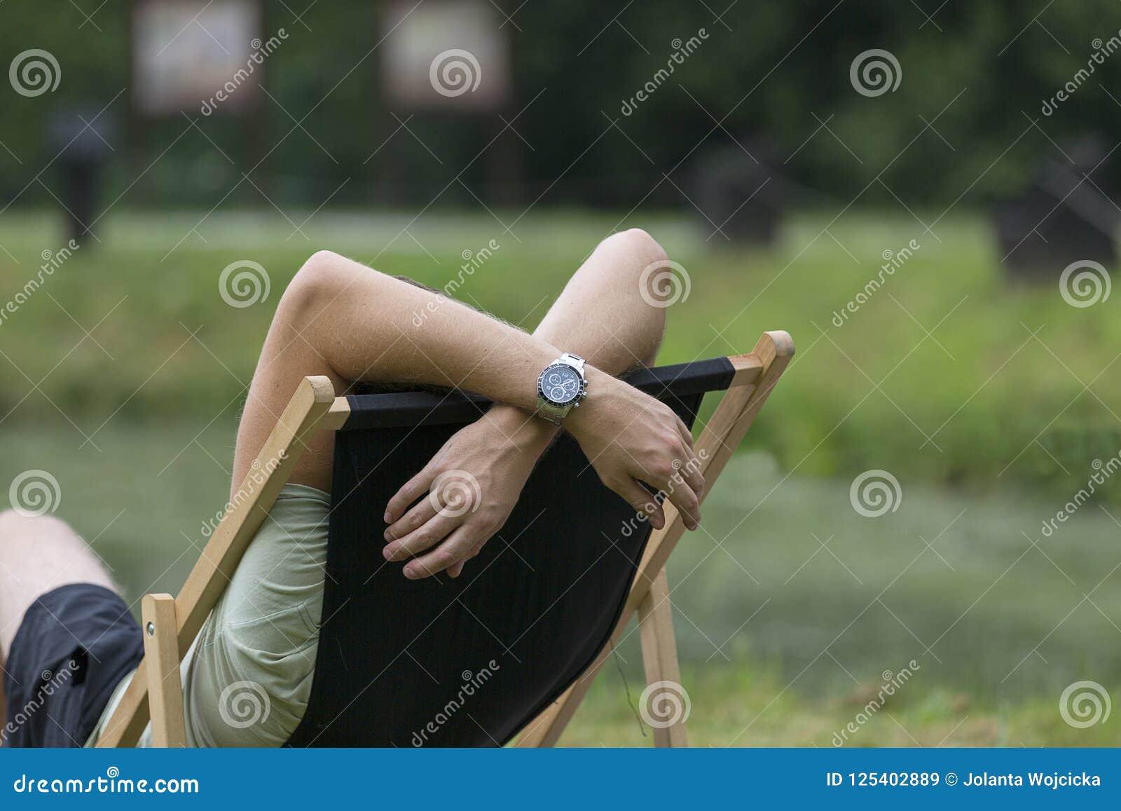 Молодой человек лежа на deckchair в саде, ослабляет, выходной день