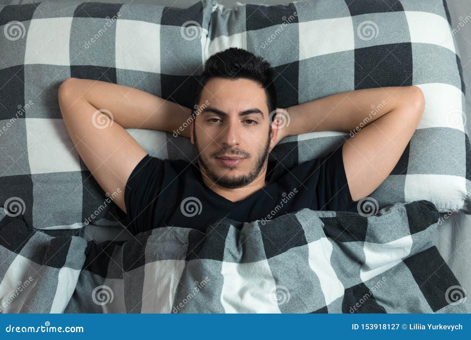 Молодой человек лежит в кровати Он счастлив, взгляд на камере
