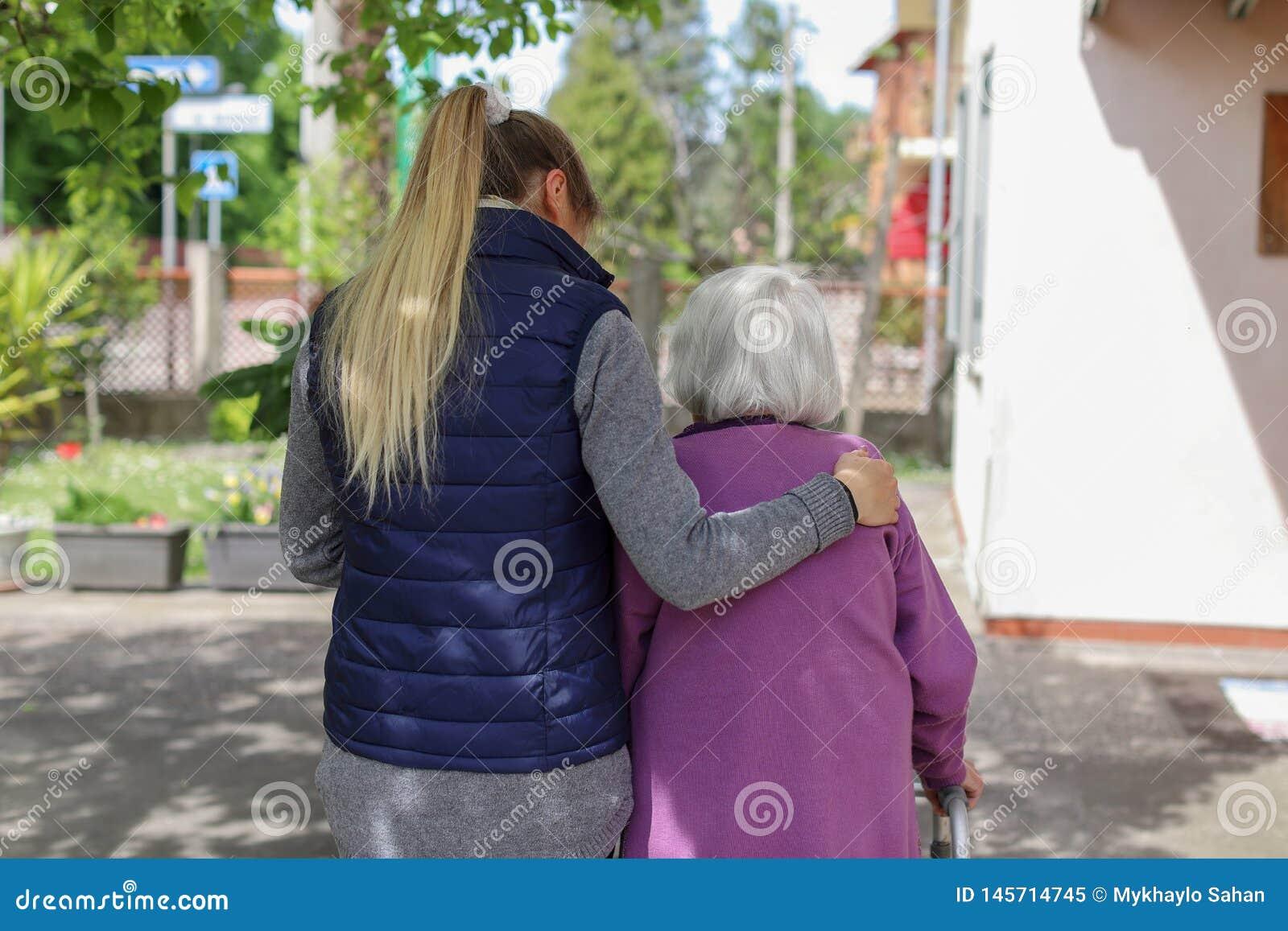 Молодой человек осуществляющий уход идя с пожилой женщиной в саде