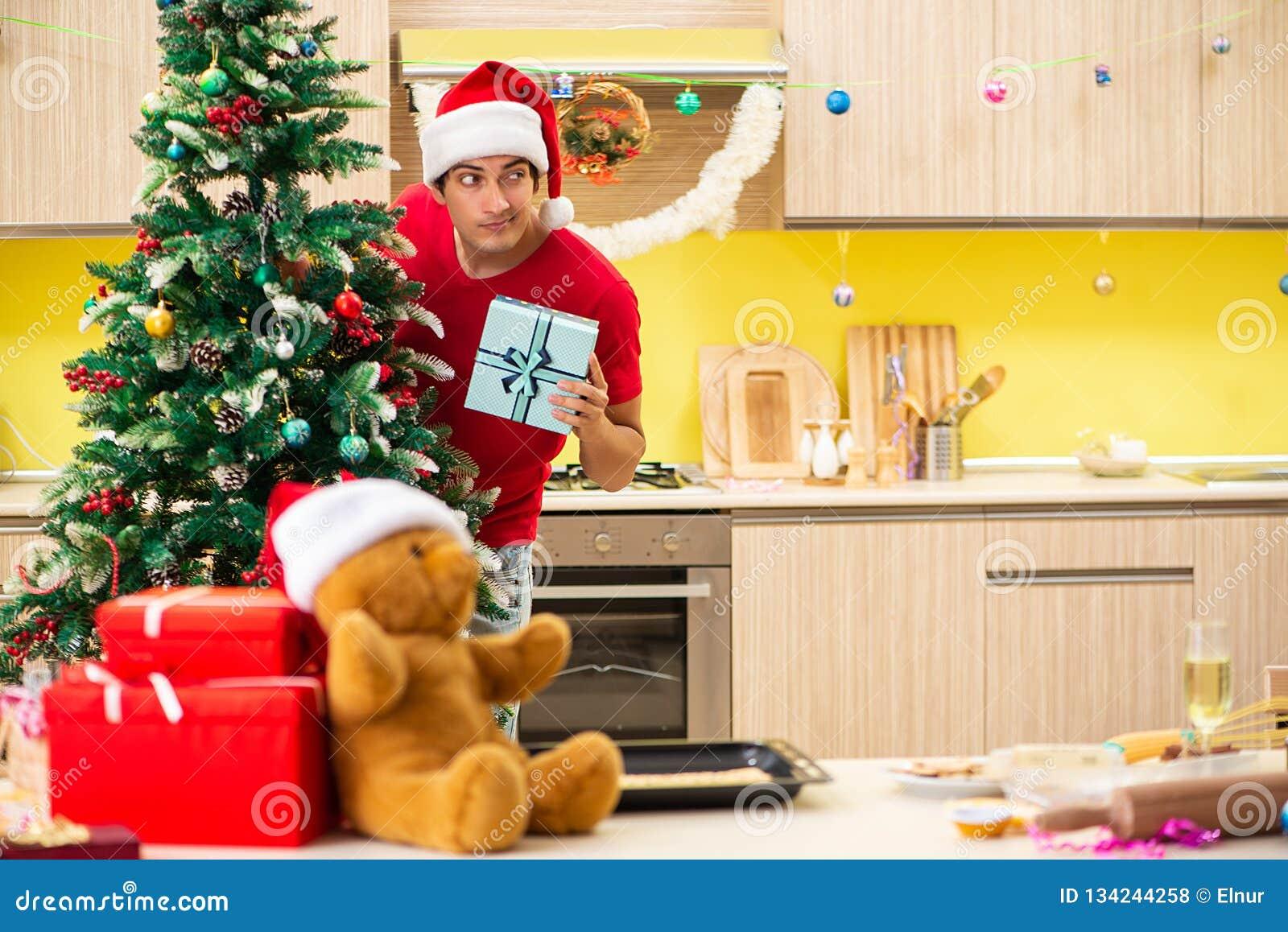 Молодой человек празднуя рождество в кухне