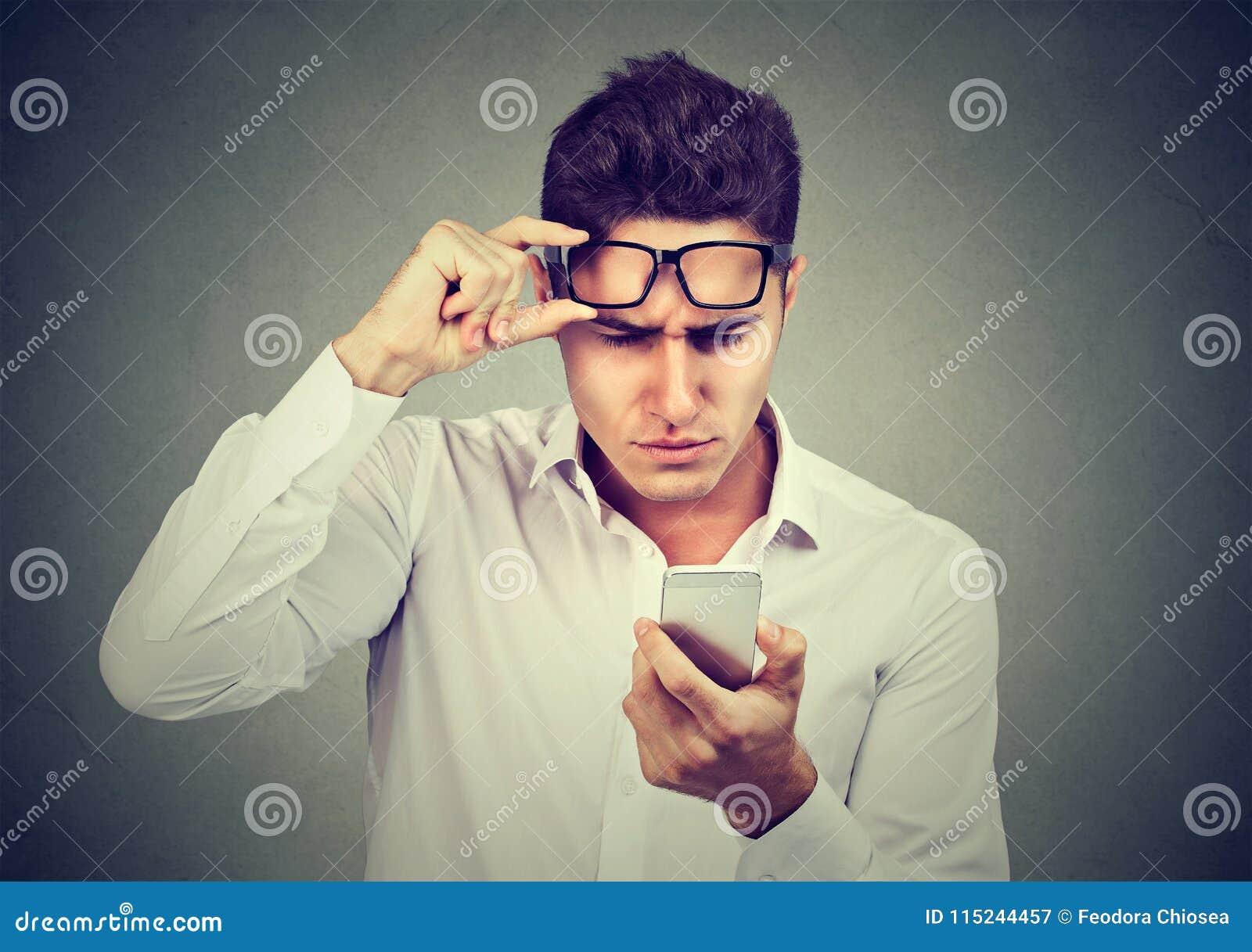 Молодой человек при стекла имея тревогу видя сотовый телефон имеет проблемы зрения Плохое текстовое сообщение