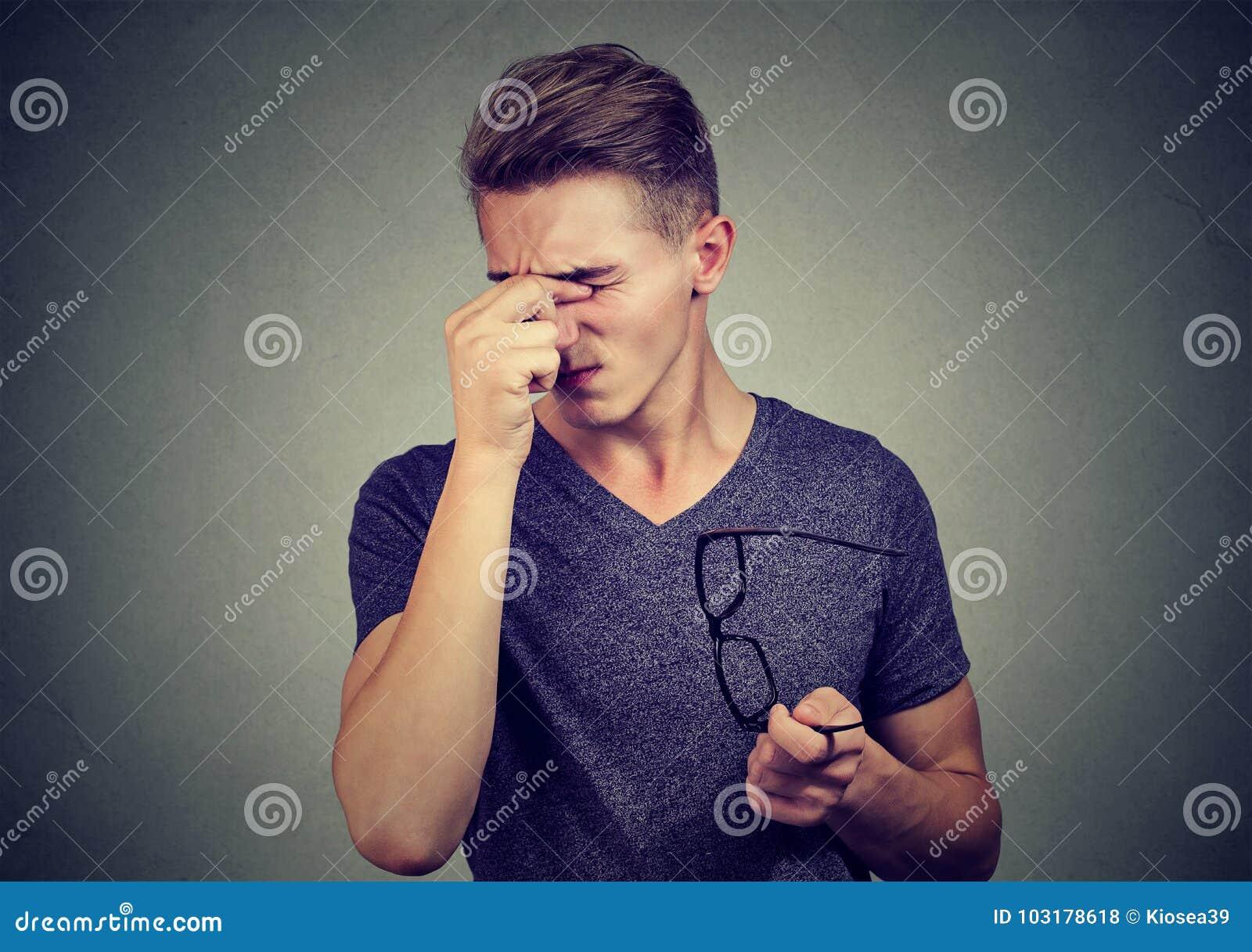 Молодой человек при стекла страдая от Ня напряжен зрения
