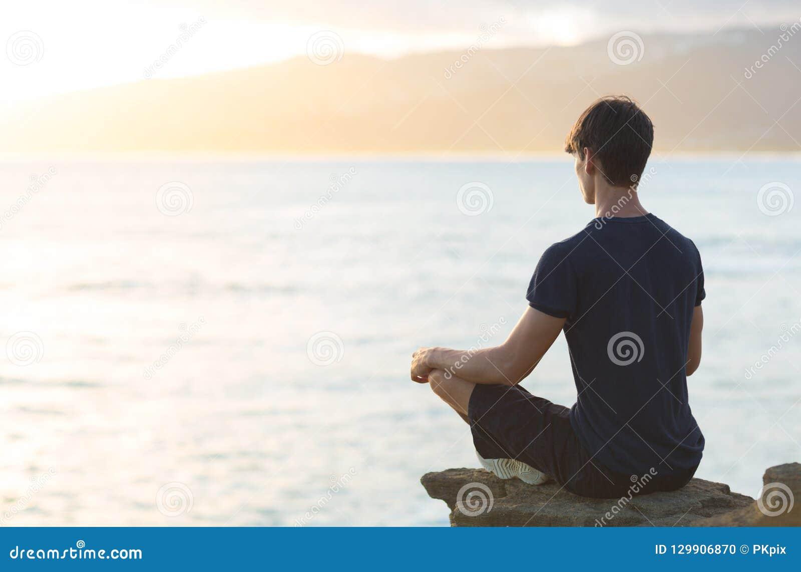 Молодой человек размышляя на верхней скале океана во время захода солнца