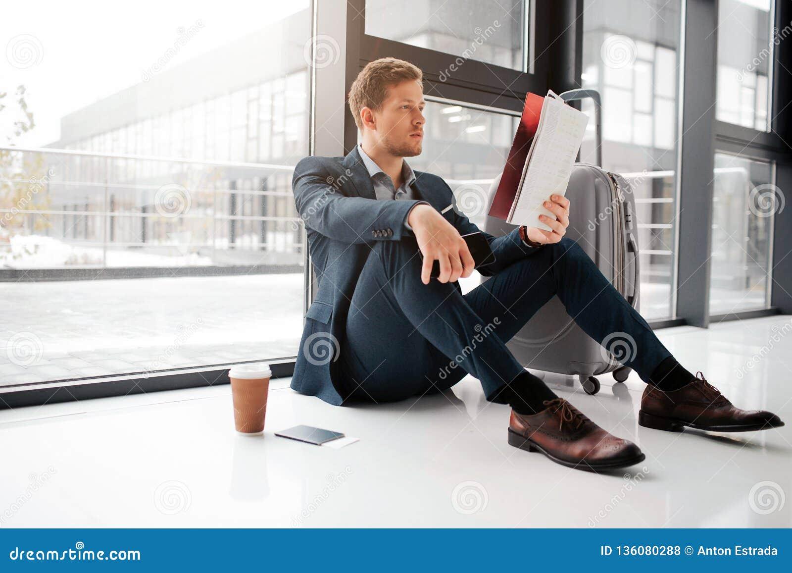 Молодой человек сидит на поле и взгляде на меню кафа Стойка чашки кофе на поле с билетами в паспорте Он ждет полет