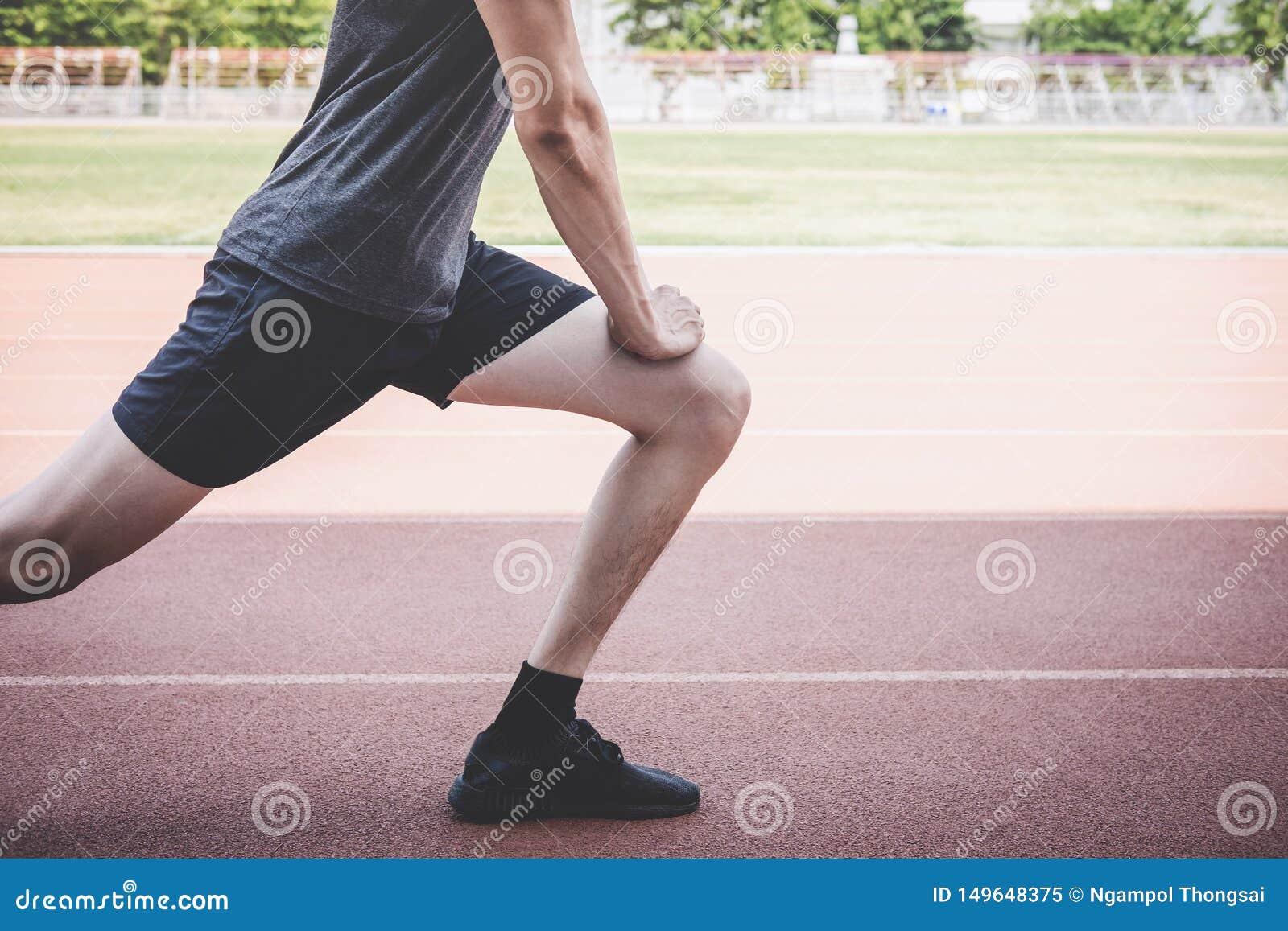 Молодой человек спортсмена фитнеса бежать на следе дороги, здоровье разминки тренировки и бегуне протягивая ноги перед, который п
