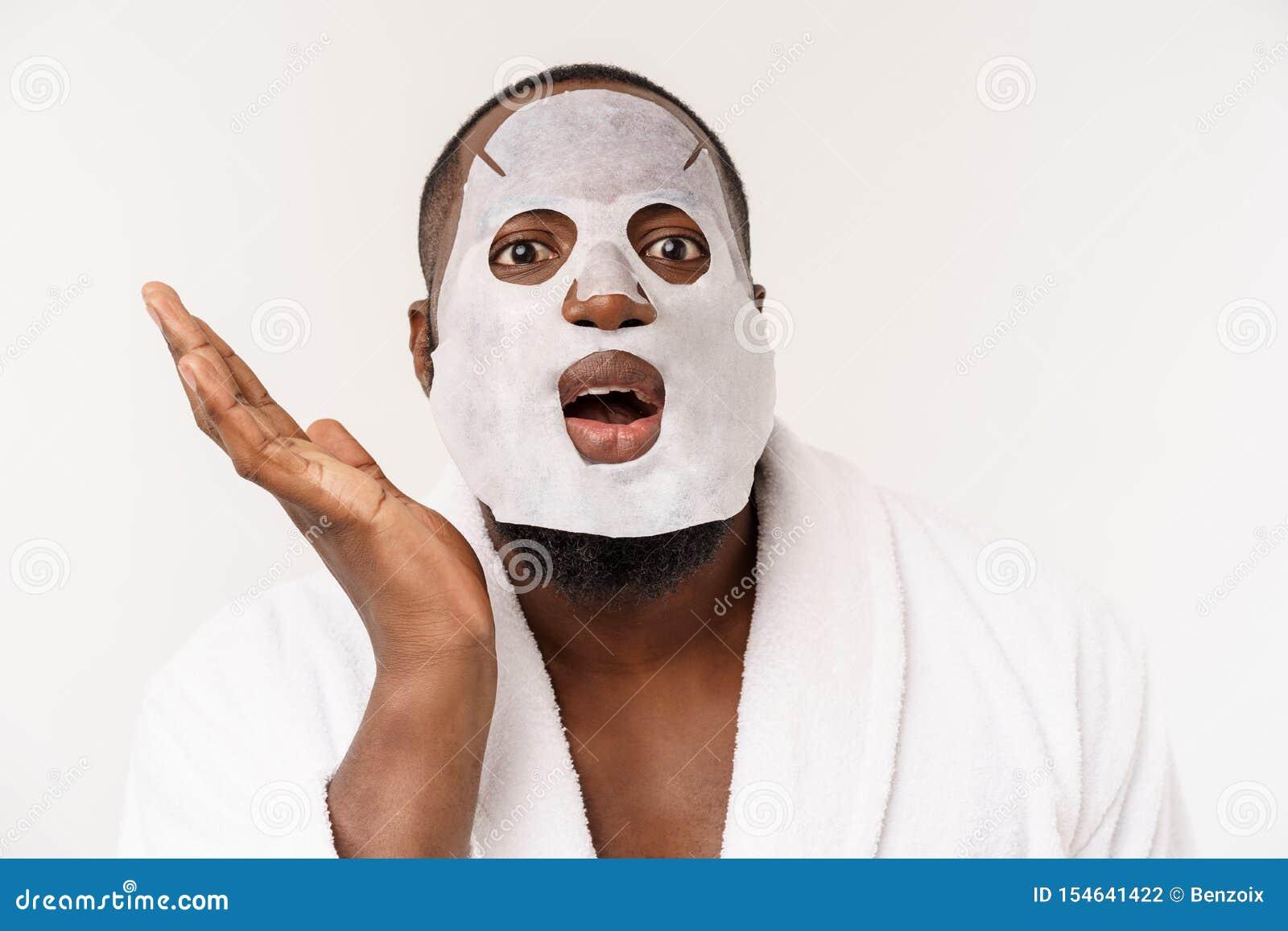 Молодой человек с бумажной маской на стороне смотря сотрясенный с открытым ртом, изолированным на белой предпосылке
