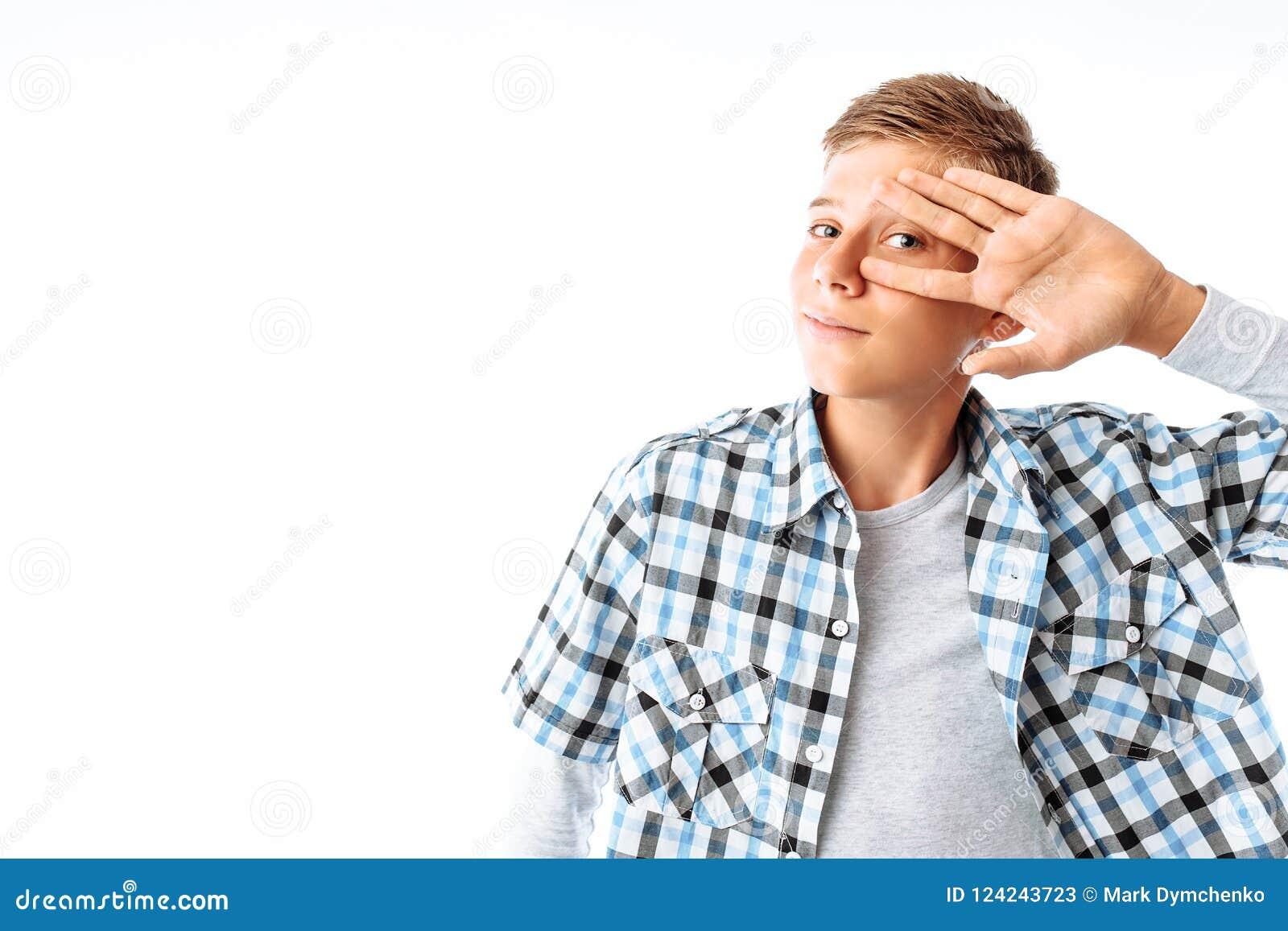 Молодой человек с заботливым взглядом, парень держа его руку около его стороны, мальчик с стеклами в студии на белой предпосылке,