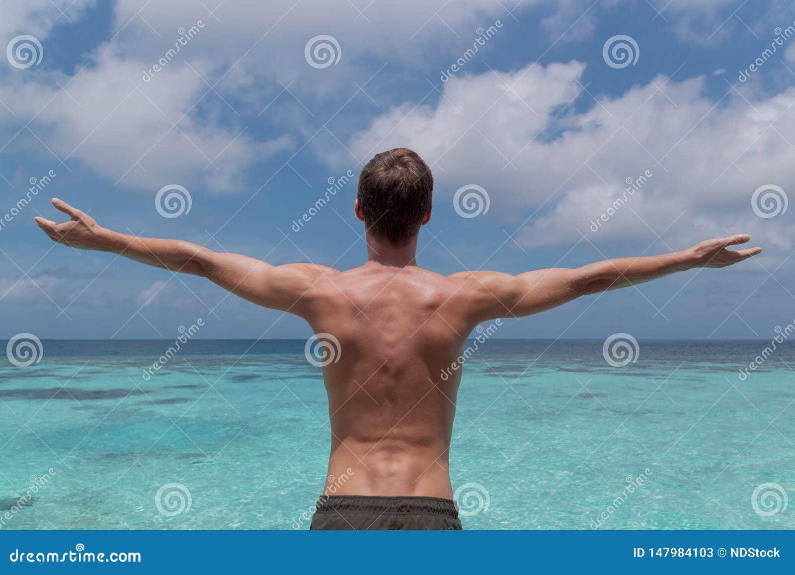 Молодой человек с оружиями поднятыми перед ясным открытым морем в тропическом назначении праздника