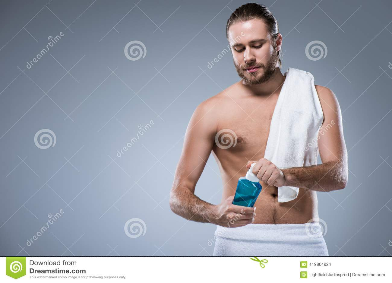 Молодой человек с полотенцем ванны на его плече держа бутылку с rinse зуба в руках,