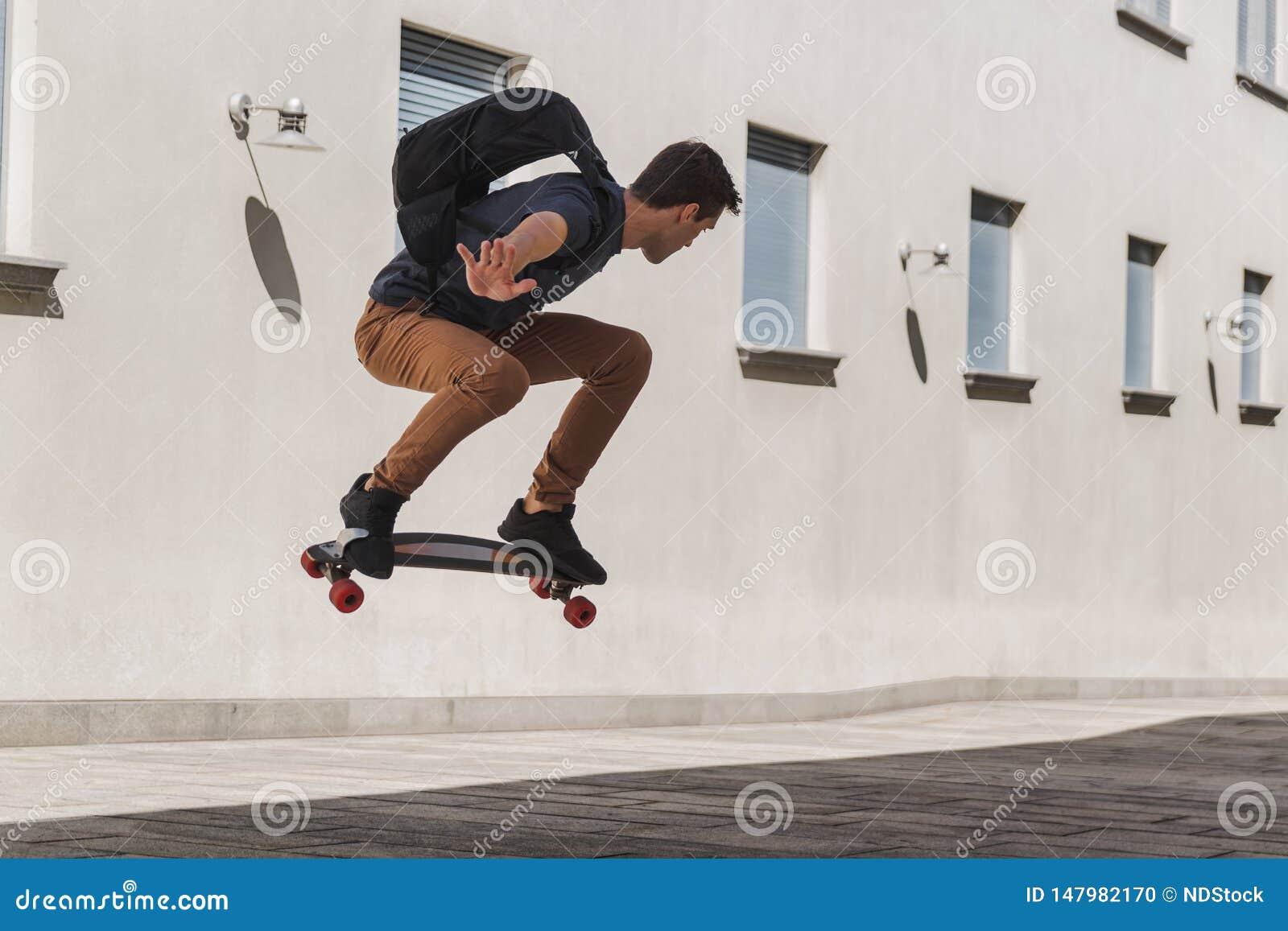 Молодой человек с рюкзаком используя longboard и скакать когда он пойдет обучить после летних отпусков