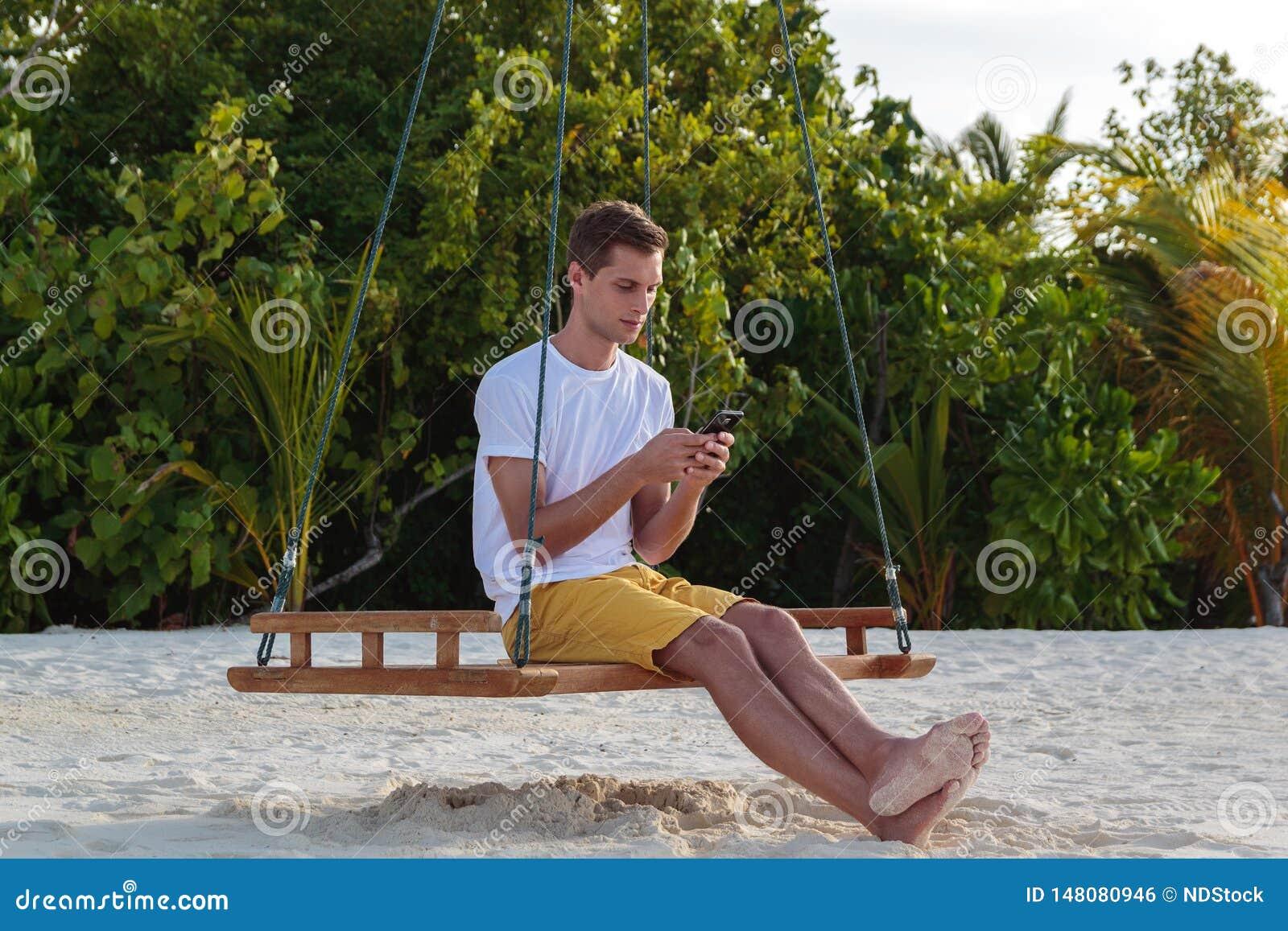 Молодой человек усаженный на качание и использование его телефона Белые песок и джунгли как предпосылка
