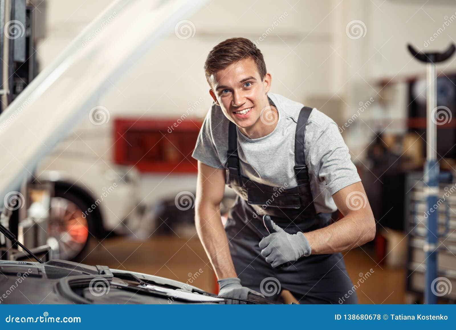 Молодой человек усмехаясь положение около автомобиля на его работе Обслуживание автомобиля и корабля