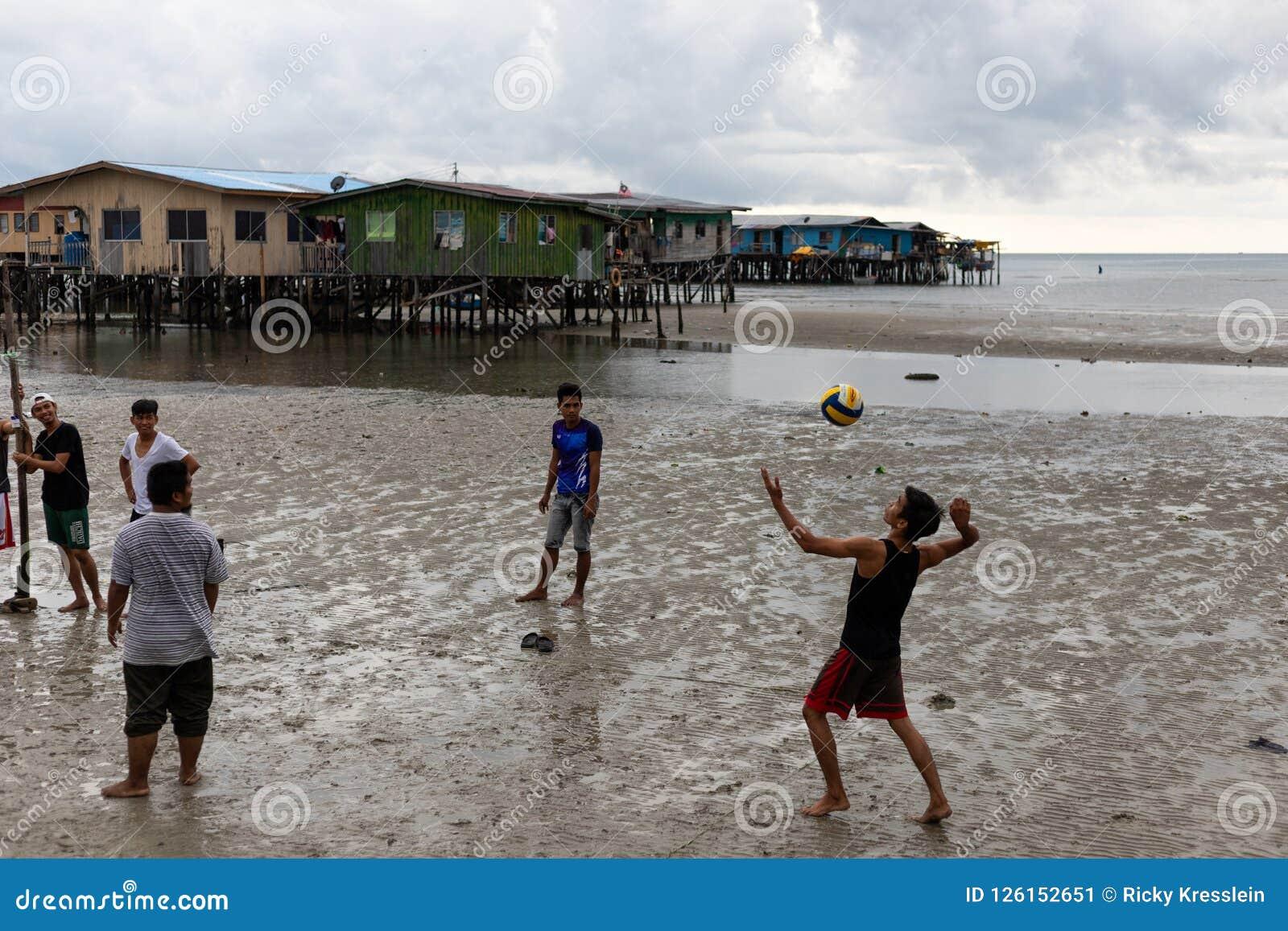 Молодой человек Povert азиатского городка стороны моря волейбола сервировки мальчика плохой
