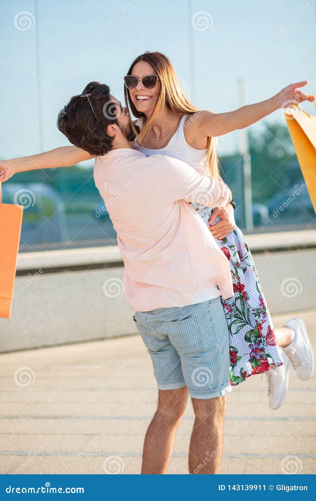 Молодой шаловливый человек закручивая его девушку в воздухе