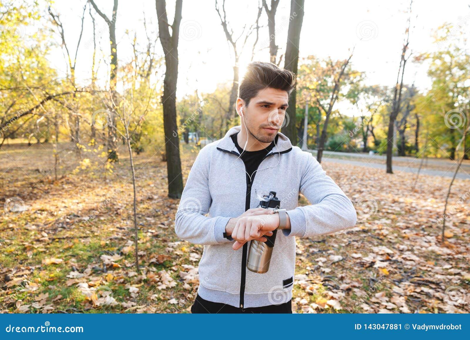 Молодой outdoors спортсмена в музыке парка слушая с питьевой водой наушников смотря дозор
