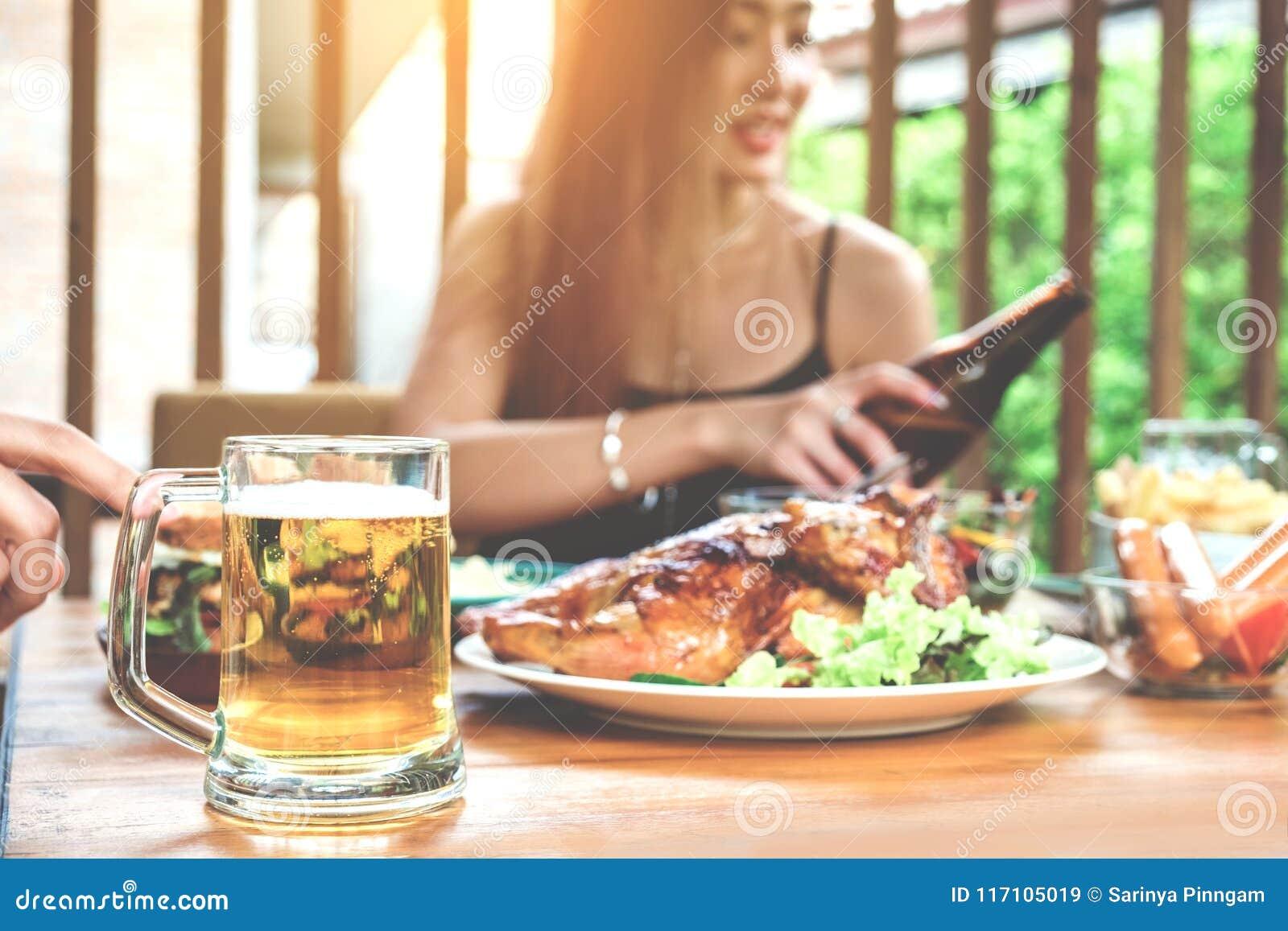 Молодые азиатские женщины выпивая стекла пива и clink счастливые пока en