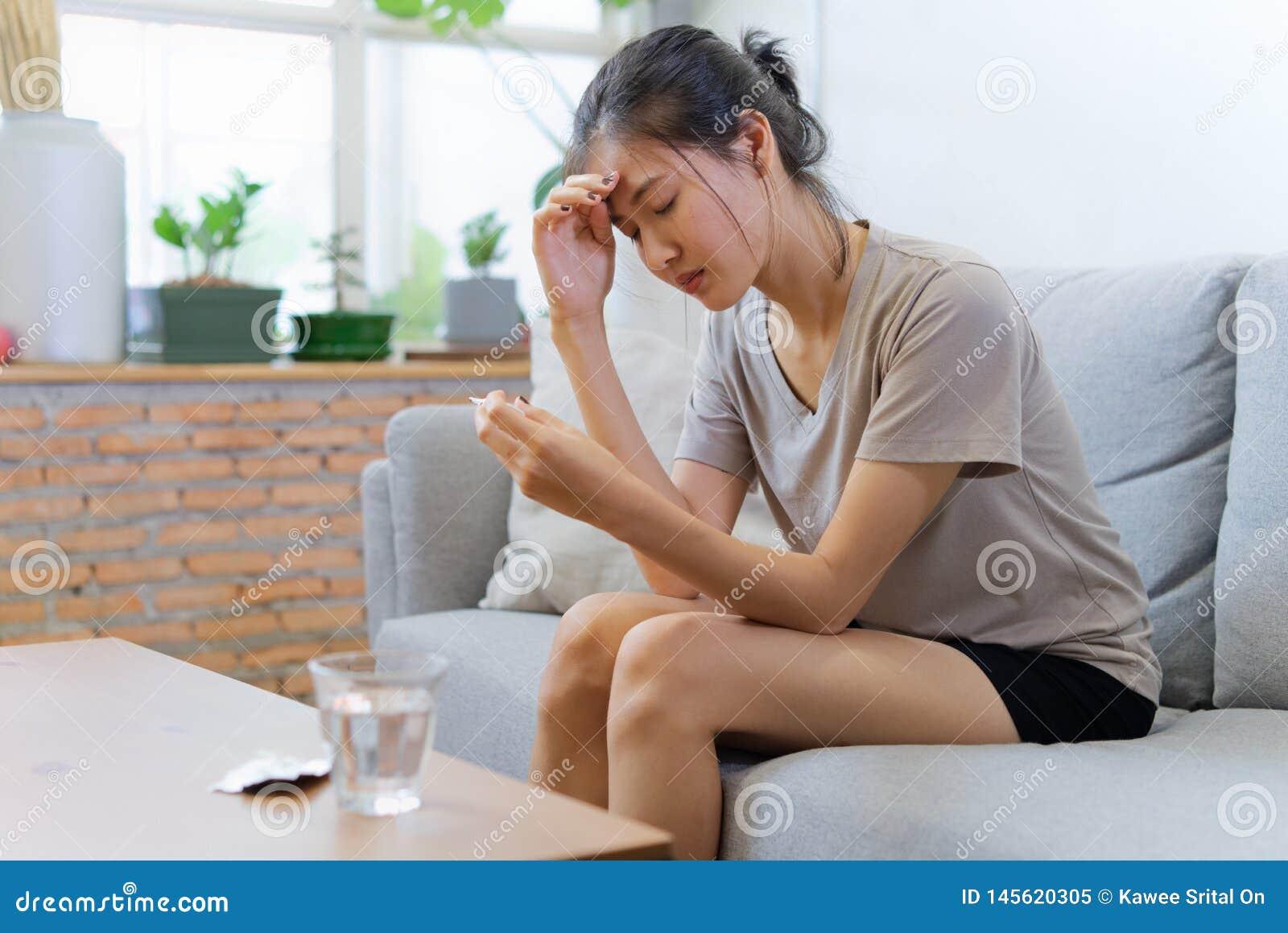Молодые азиатские женщины на софе закрывая ее глаза страдают от головной боли и имеют некоторую лихорадку