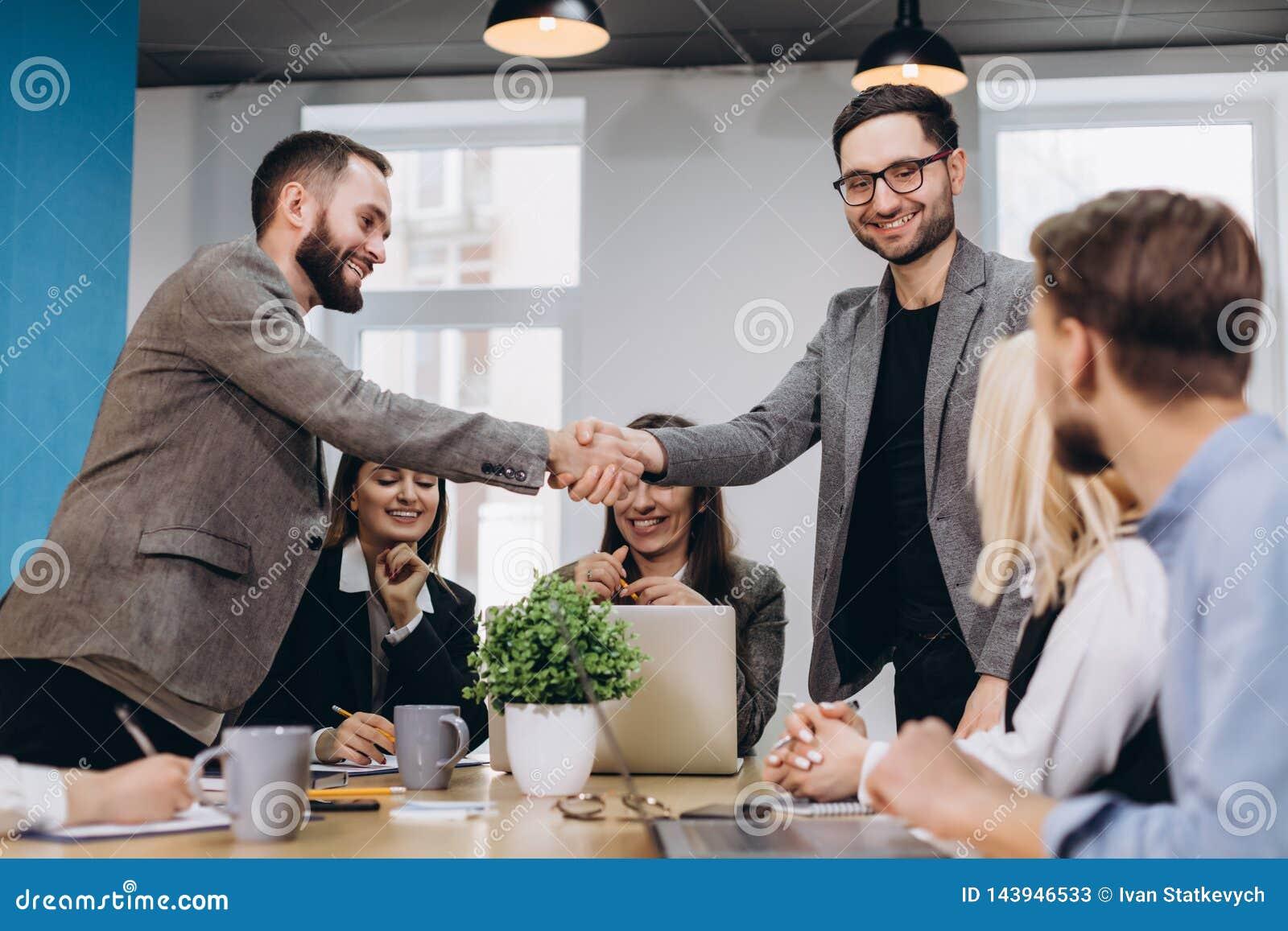 Молодые бизнесмены тряся руки в офисе Заканчивая успешная встреча