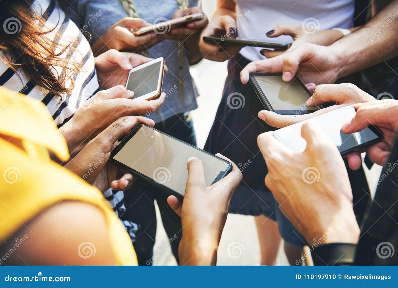 Молодые взрослые друзья используя cu молодости smartphones совместно outdoors