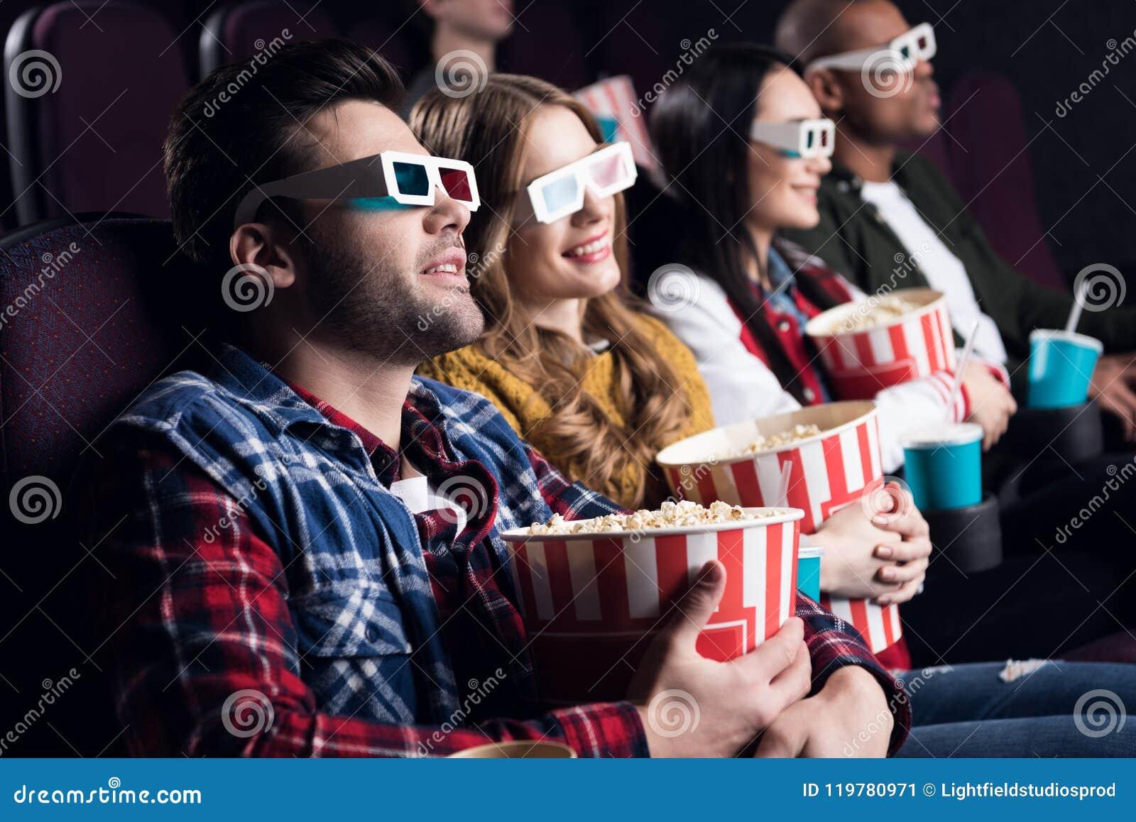 молодые друзья в стеклах 3d с попкорном и содой смотря кино