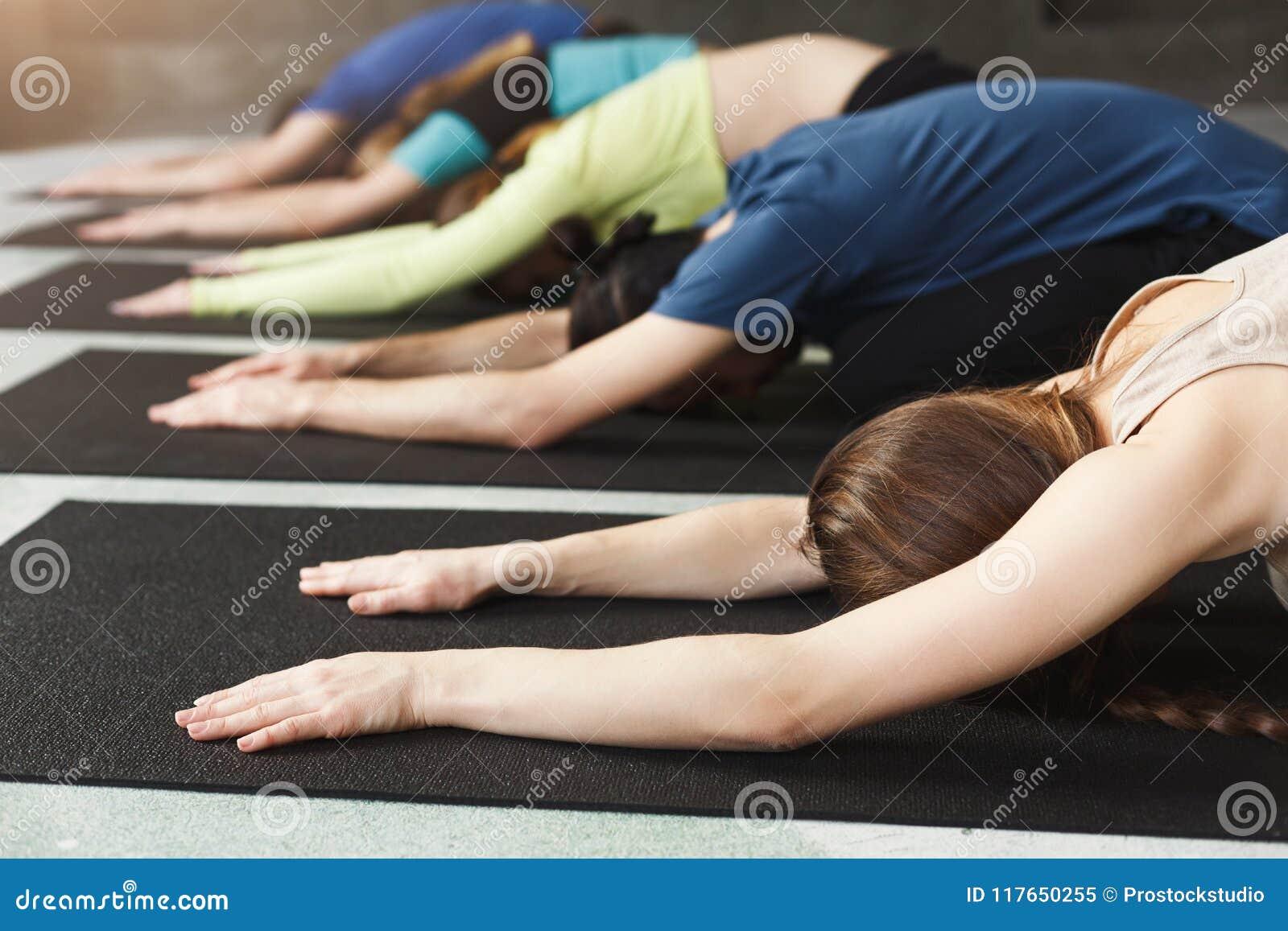 Молодые женщины и люди в занятиях йогой, ослабляют представление раздумья