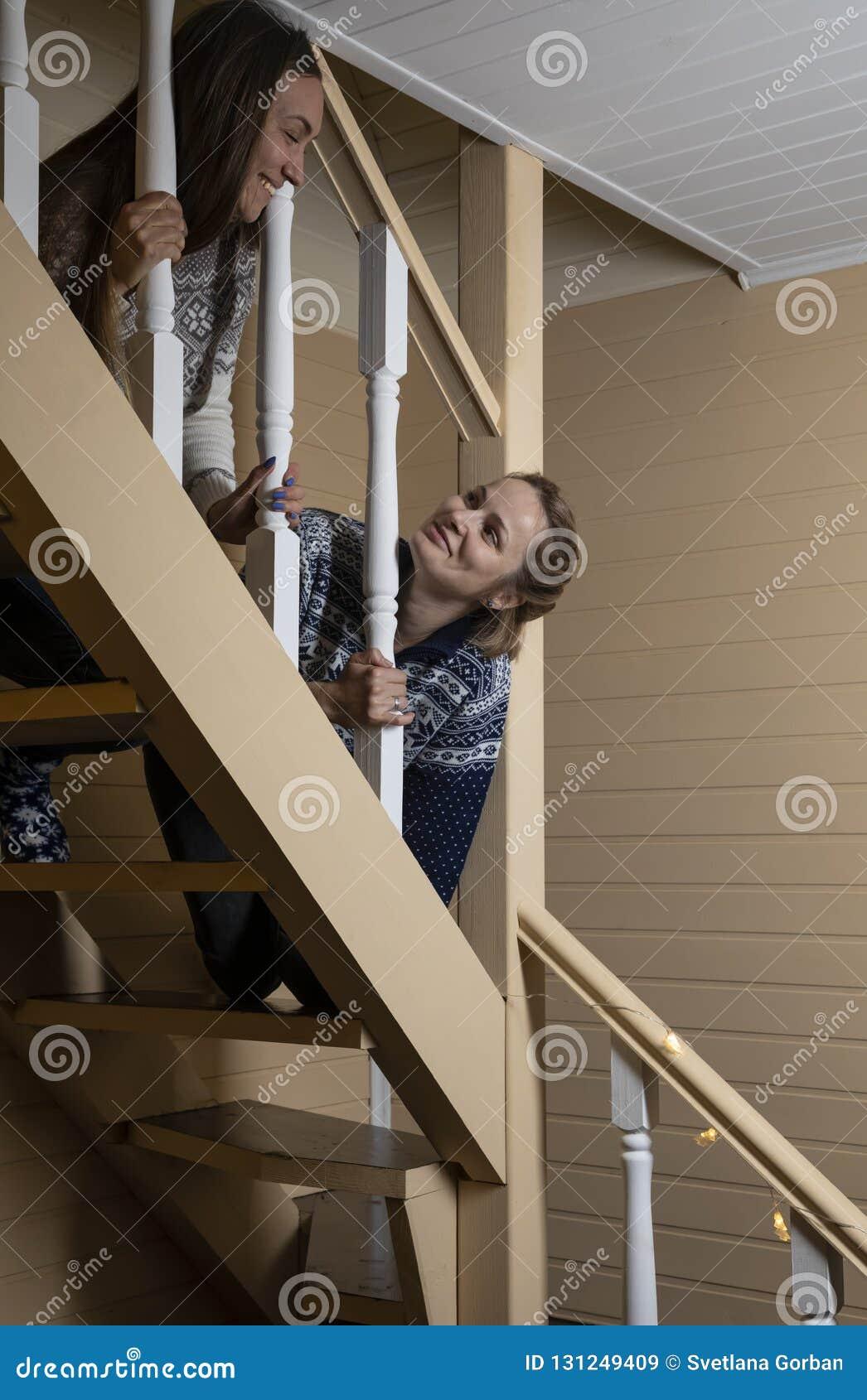 Молодые женщины украшают лестницы и смех