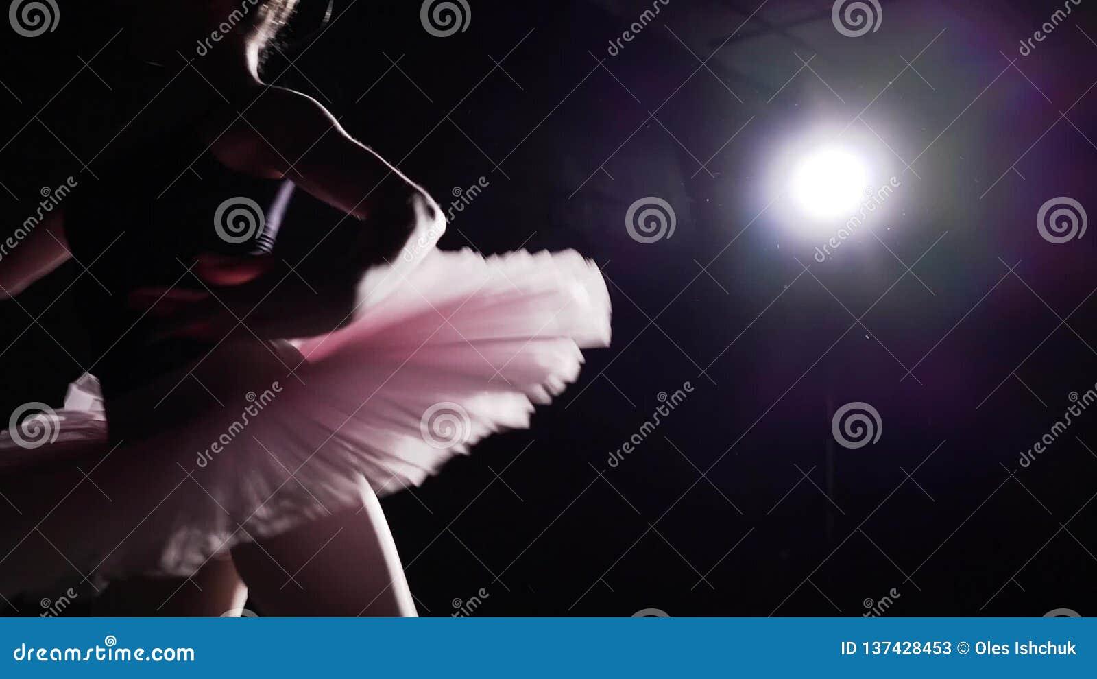 Молодые и грациозные танцы балерины на ее ботинках балета pointe в фаре на черной предпосылке в студии Выставки женщины сток-видео