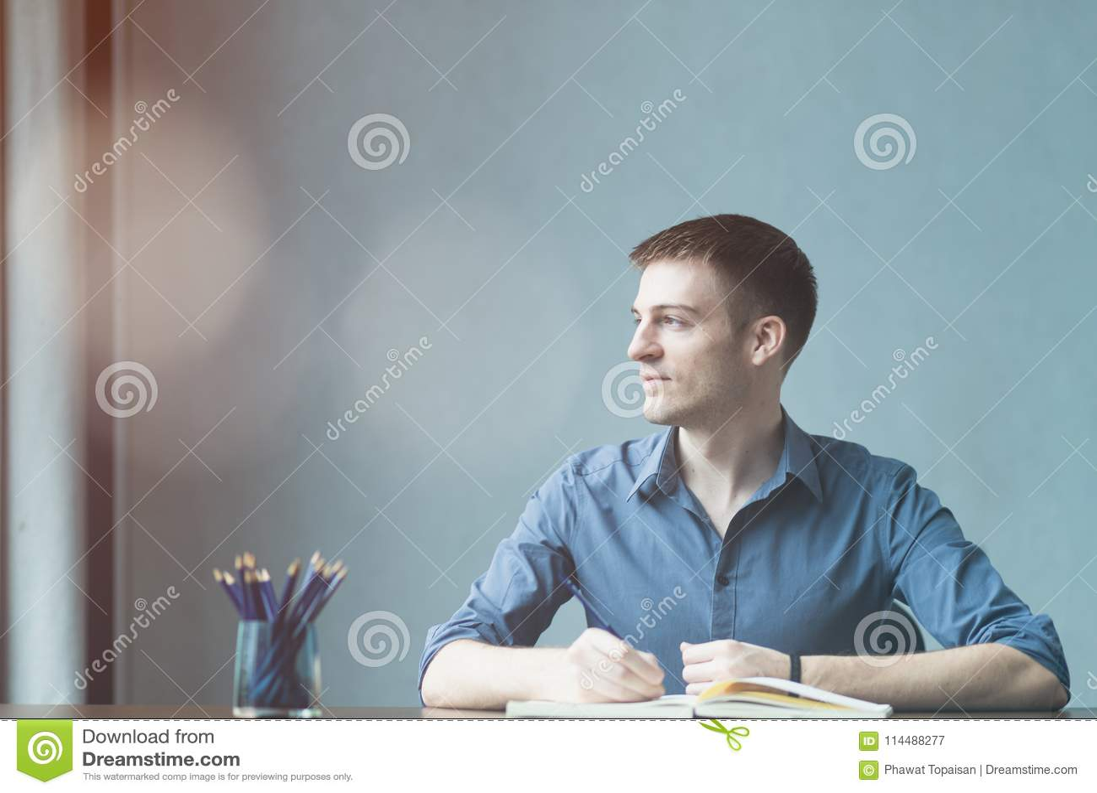 Молодые кавказцы бизнесмена сидя на таблице офиса стола и принимая примечания в тетради Пишущ и смотрящ вне окно