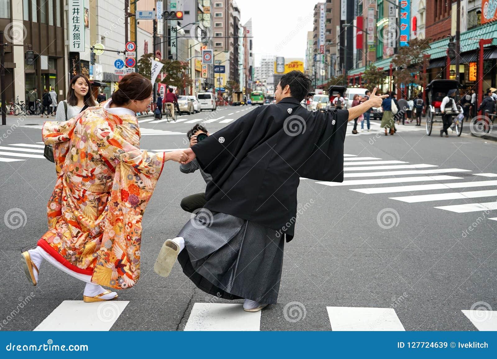 Молодые красивые японские пары одели в национальных японских костюмах и сфотографировали на токио города улицы, Японии