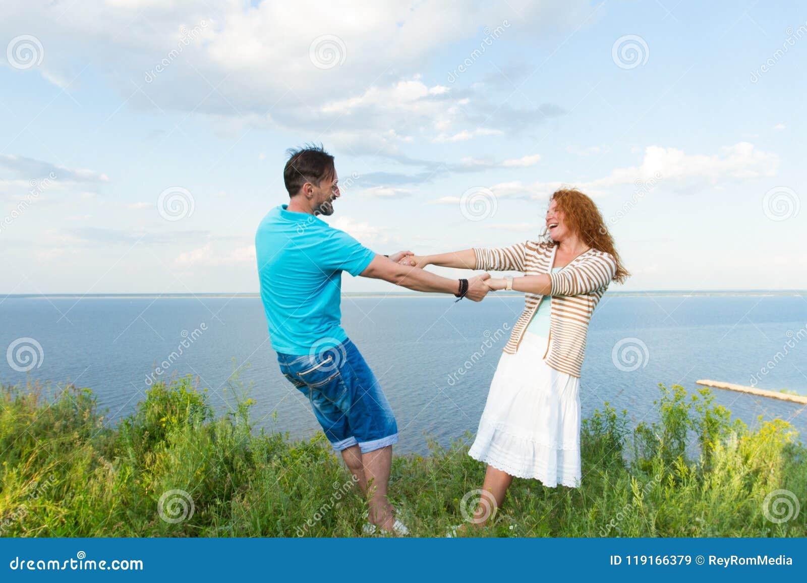 Молодые любя усмехаясь пары в траве на предпосылке озера и неба Снятый привлекательных молодых красных танцев женщины волос с пар