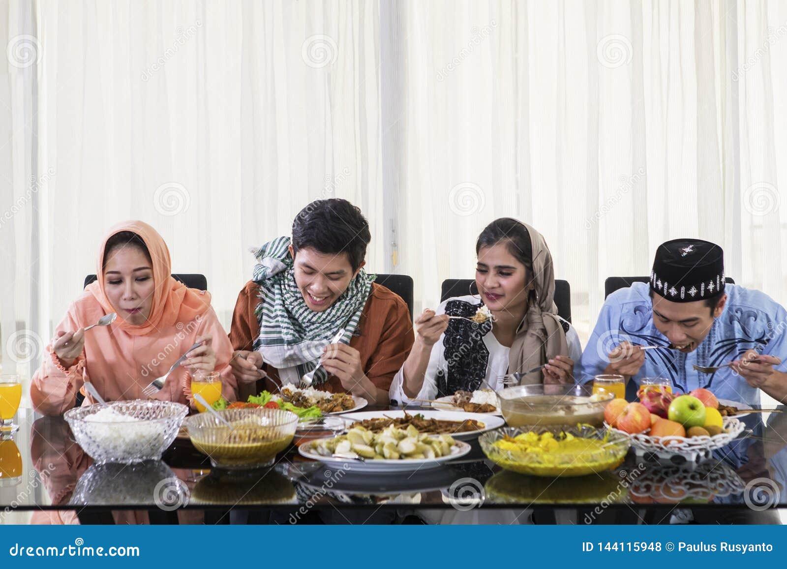 Молодые люди едят во время торжества Eid Mubarak