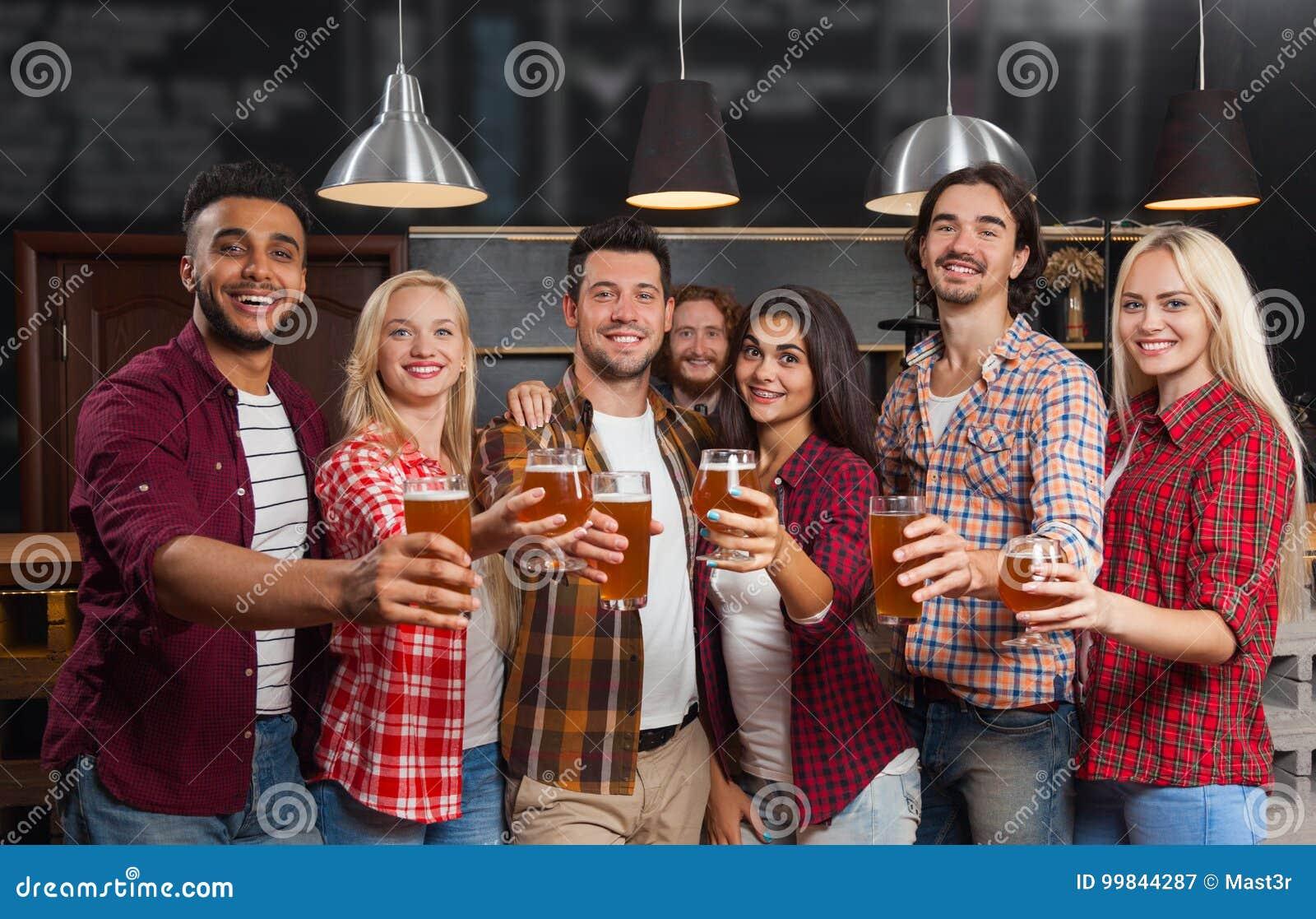 Молодые люди собирает в бар, счастливый усмехаясь паб друзей, приветственные восклицания пива питья