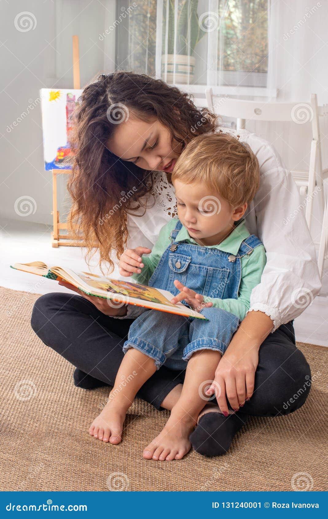 Молодые мать или няня с небольшим мальчиком ребенка сидят на поле на a