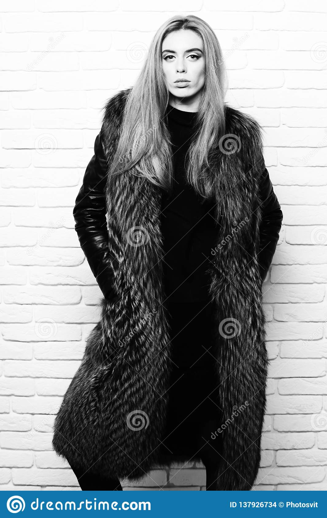 Молодые модные милые женщина или девушка с красивыми длинными светлыми волосами в пальто талии бургундского меха с чернотой
